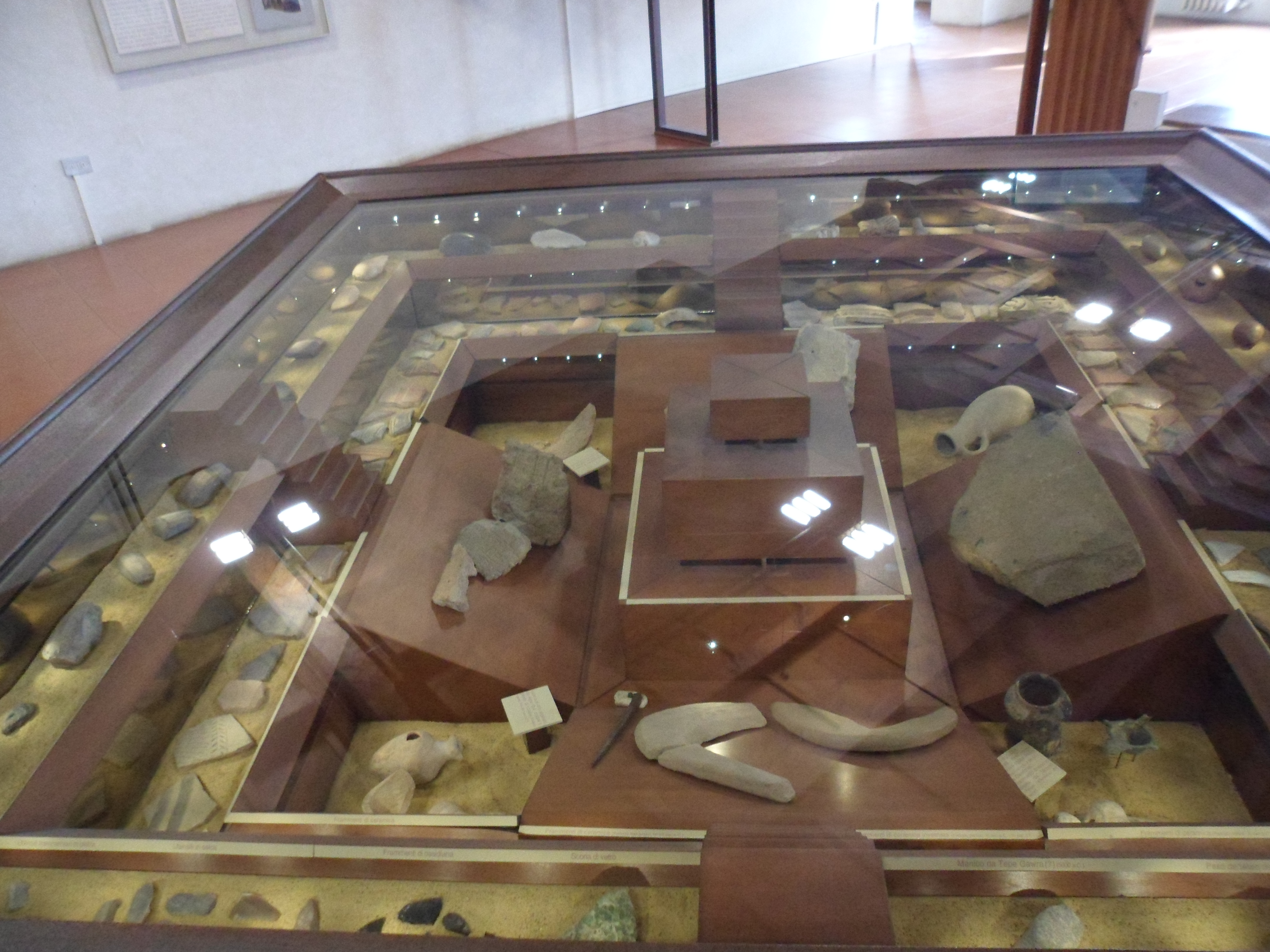 Assorted bricks, jars, seals, clay sickles, tablets, pot fragments, etc. in a depression covered in glass and shaped like a step pyramid