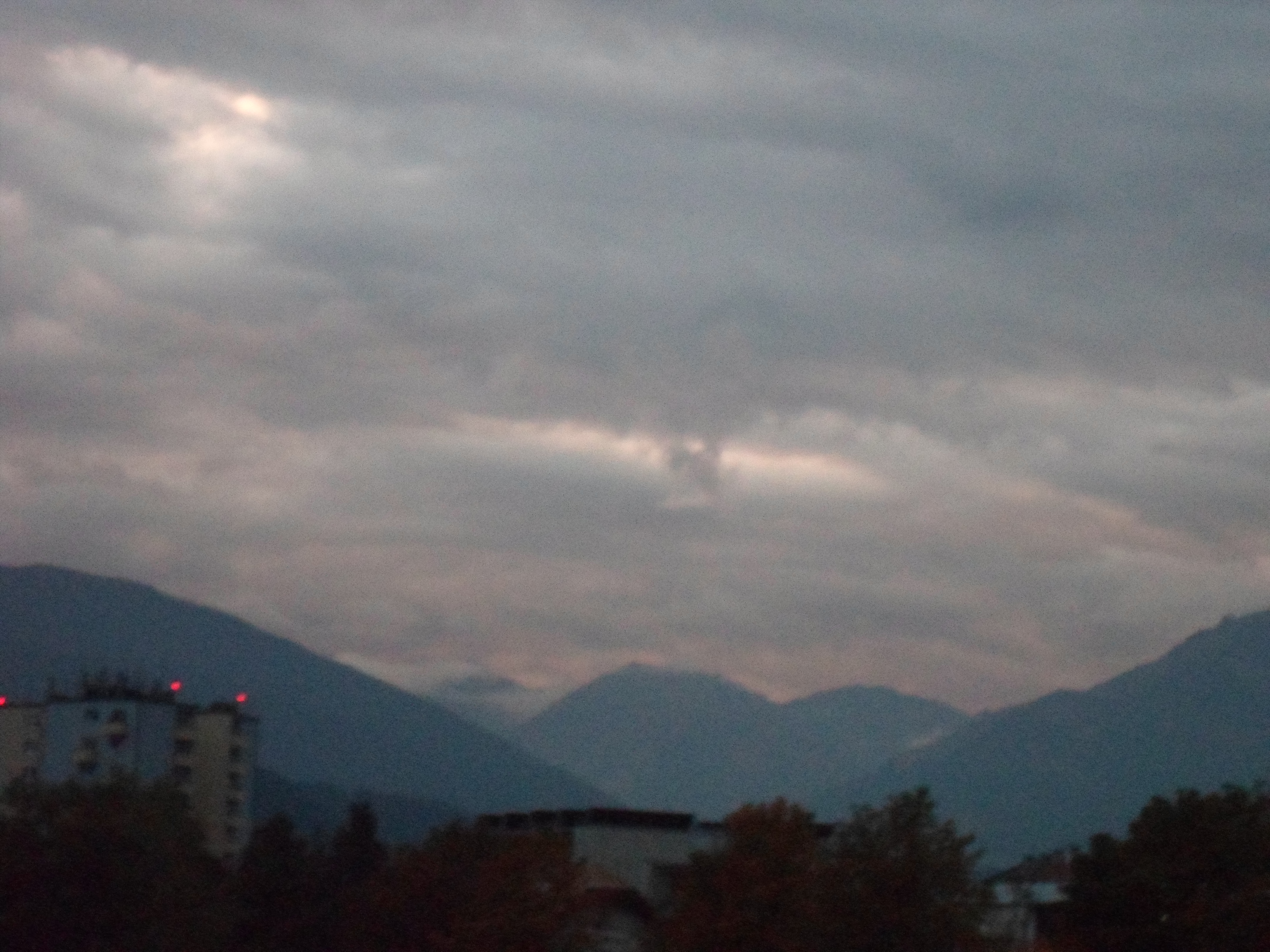 Photo of a cloudy grey sky over dark hills with a perfectly square cloud in front of the others