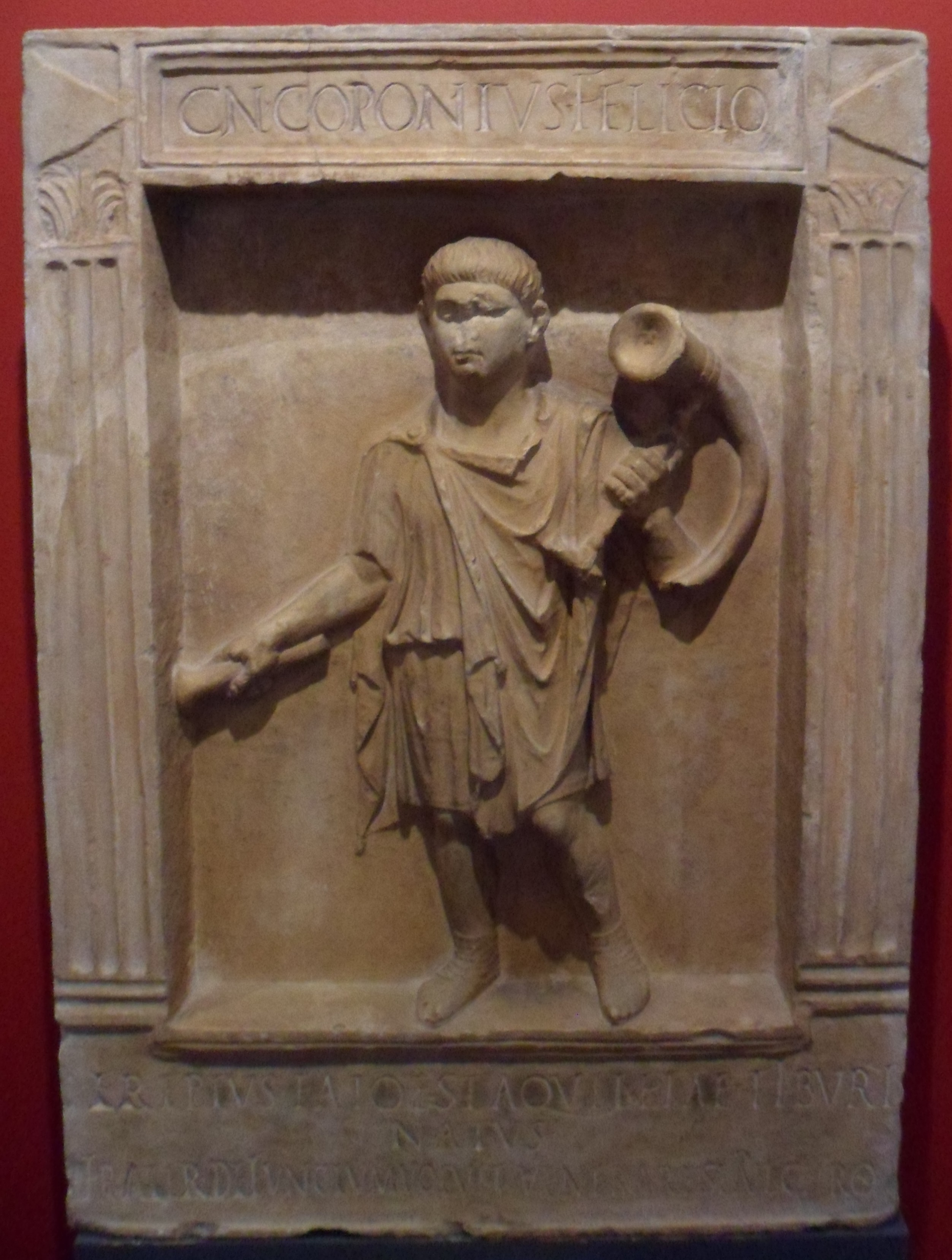 Stone panel sculpted with a man in robes carrying a horn over his right shoulder
