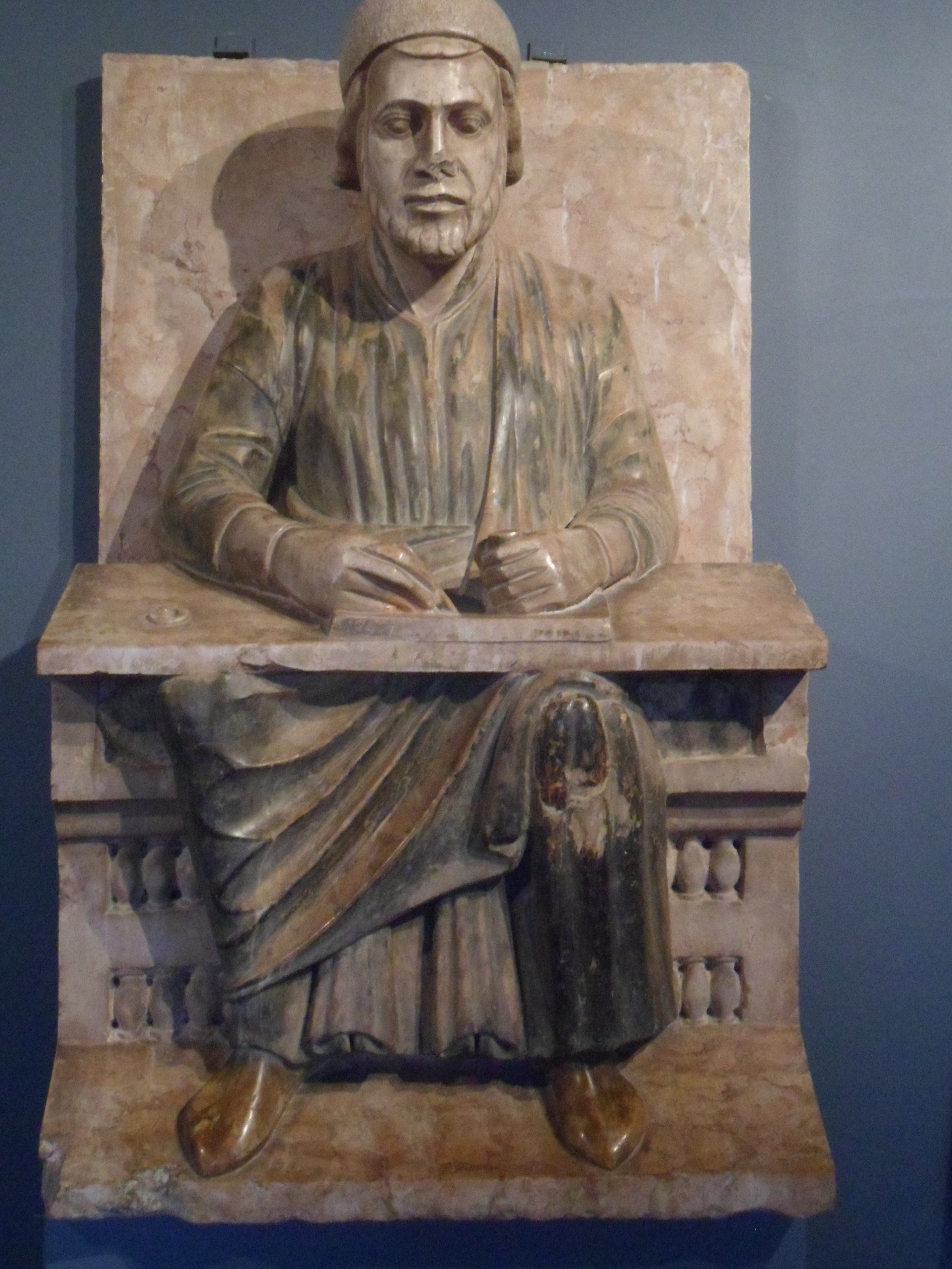 A pale red marbe statue of a man in robes and cap seated at a weighty desk