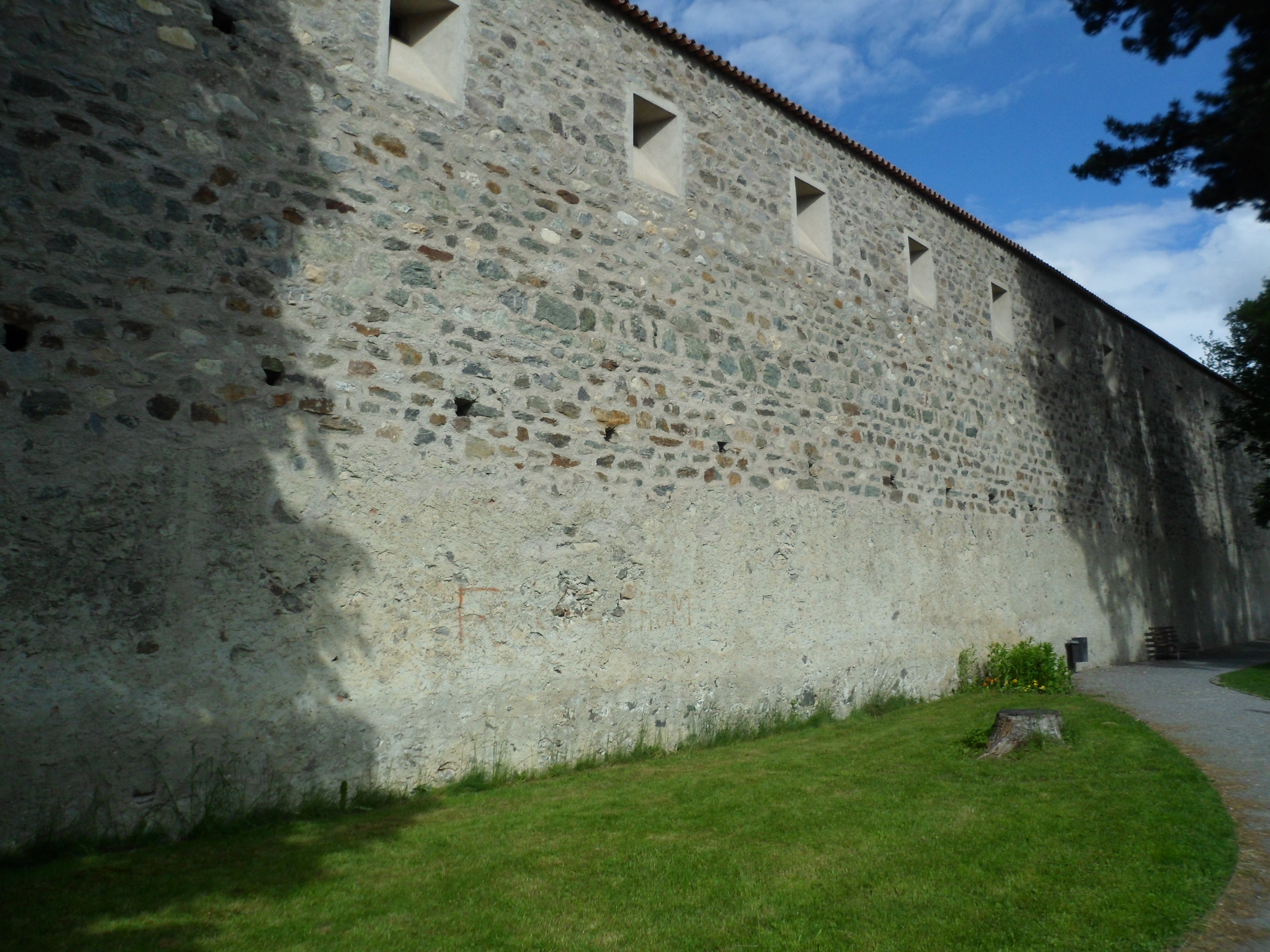 Photo of a mortared stone wall with square loopholes along the top
