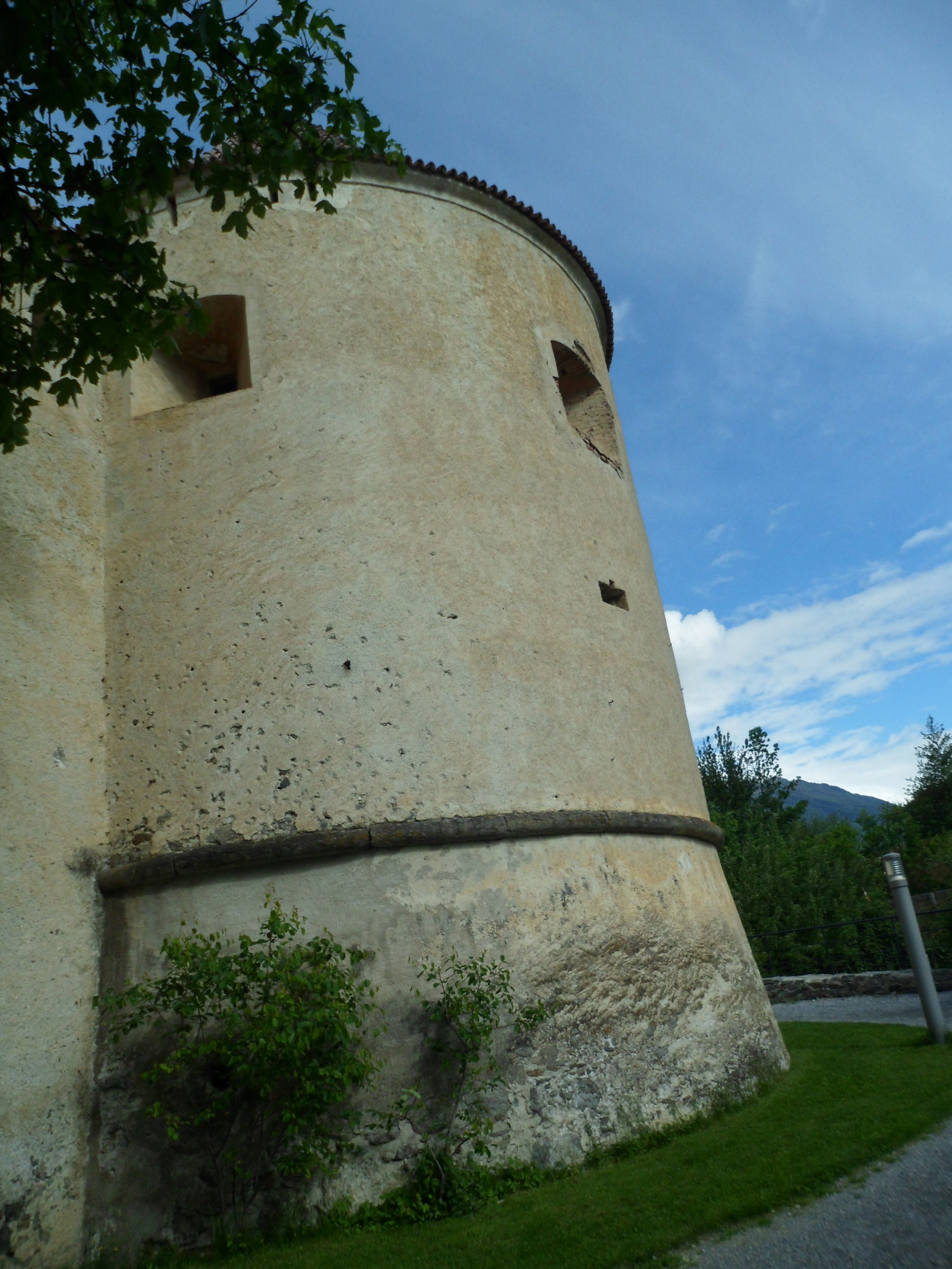 Photo of a plastered round tower with a conical roof and large loopholes near the top