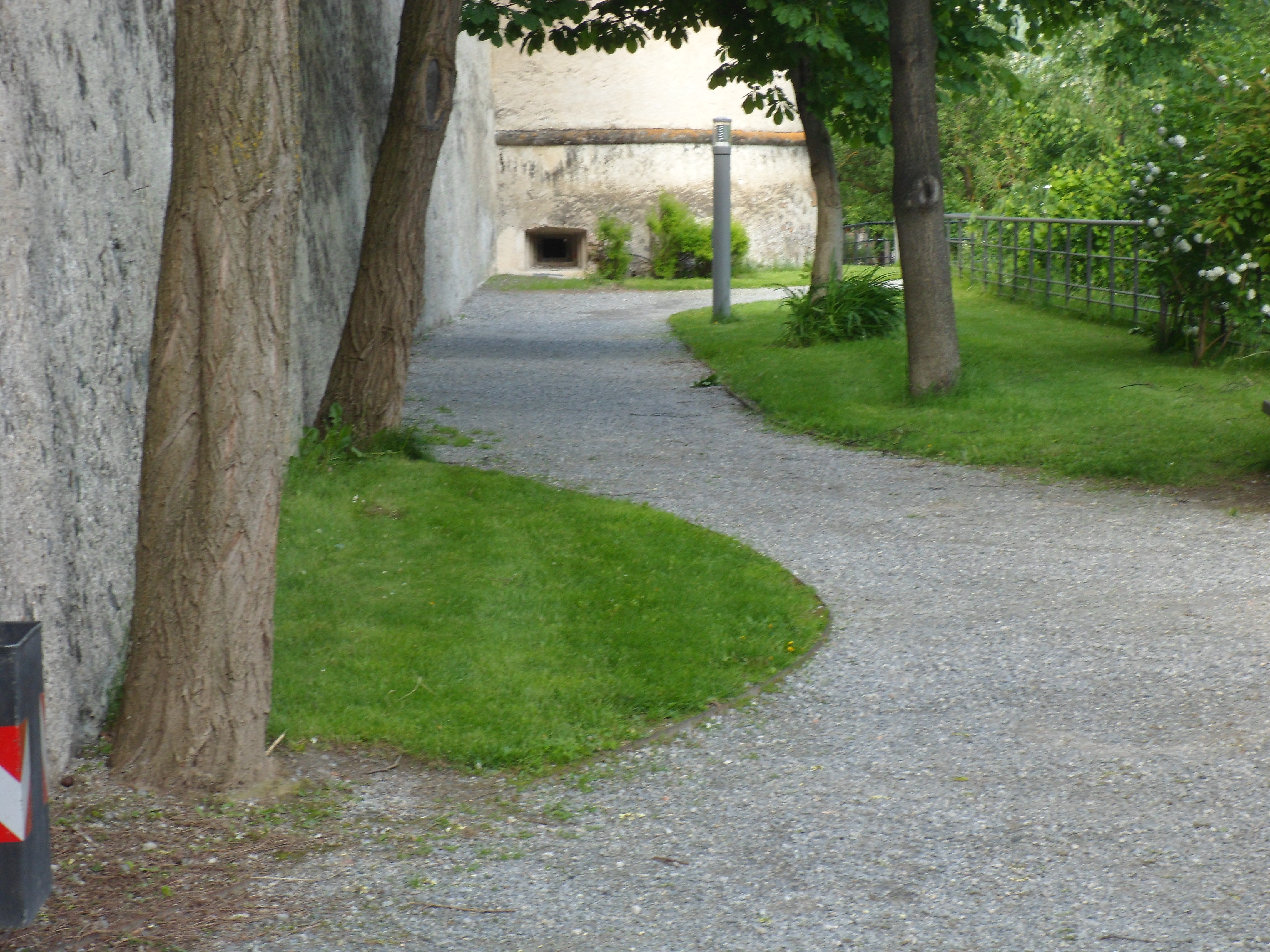 Gravel path along the base of a stone wall leading up to a round tower with a square loophole in it just above ground level.