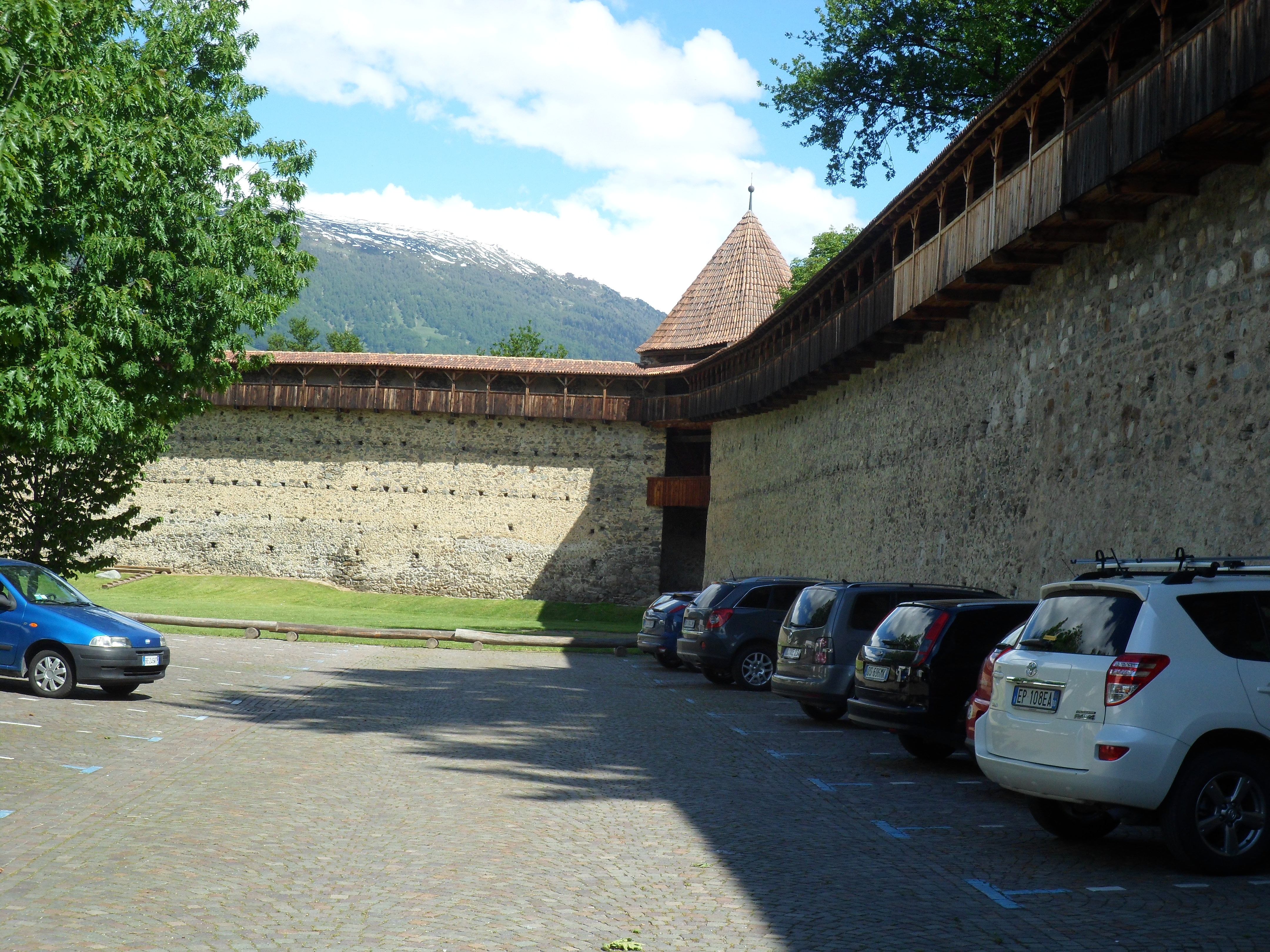 Two tall stone walls with wooden galleries along their top meet at right angles in  a round stone tower with a pointed roof and no back.  In the space between the walls are a parking lot and a green field
