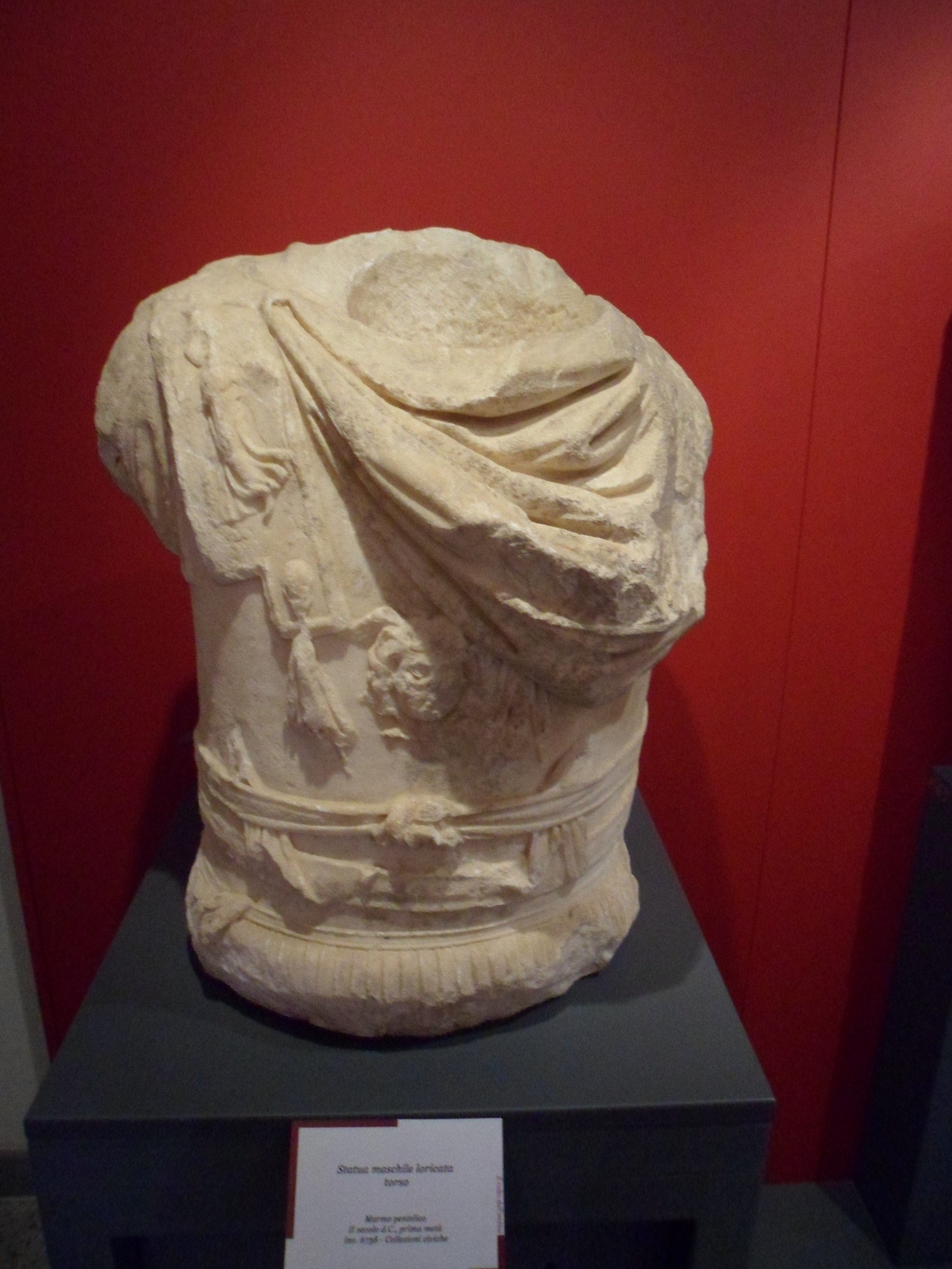 A bare marble statue of a torso in armour with shoulder flaps and a sash