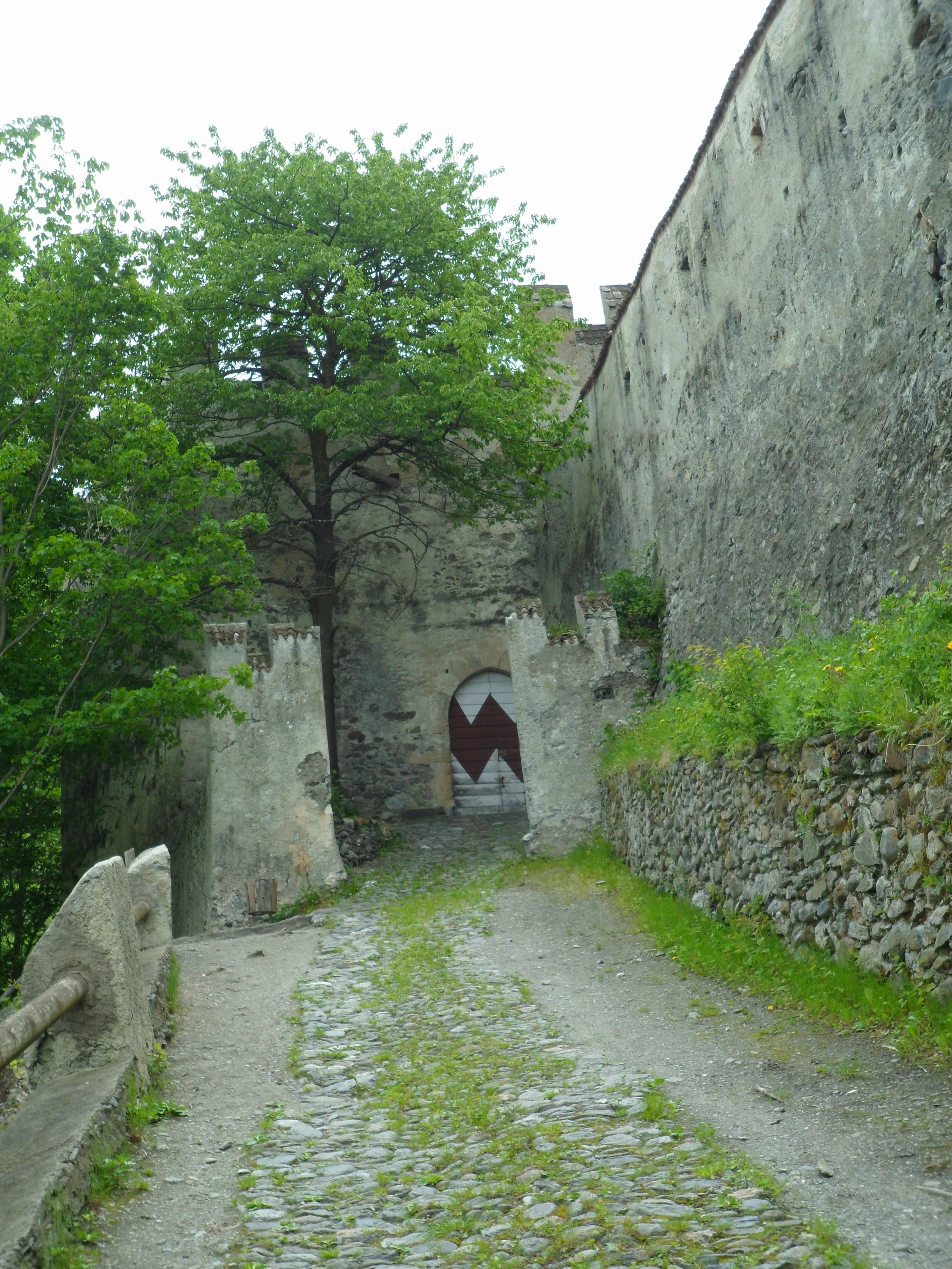 Gravel path leading up to a castle gate projecting five metres out from the tall stone wall at right
