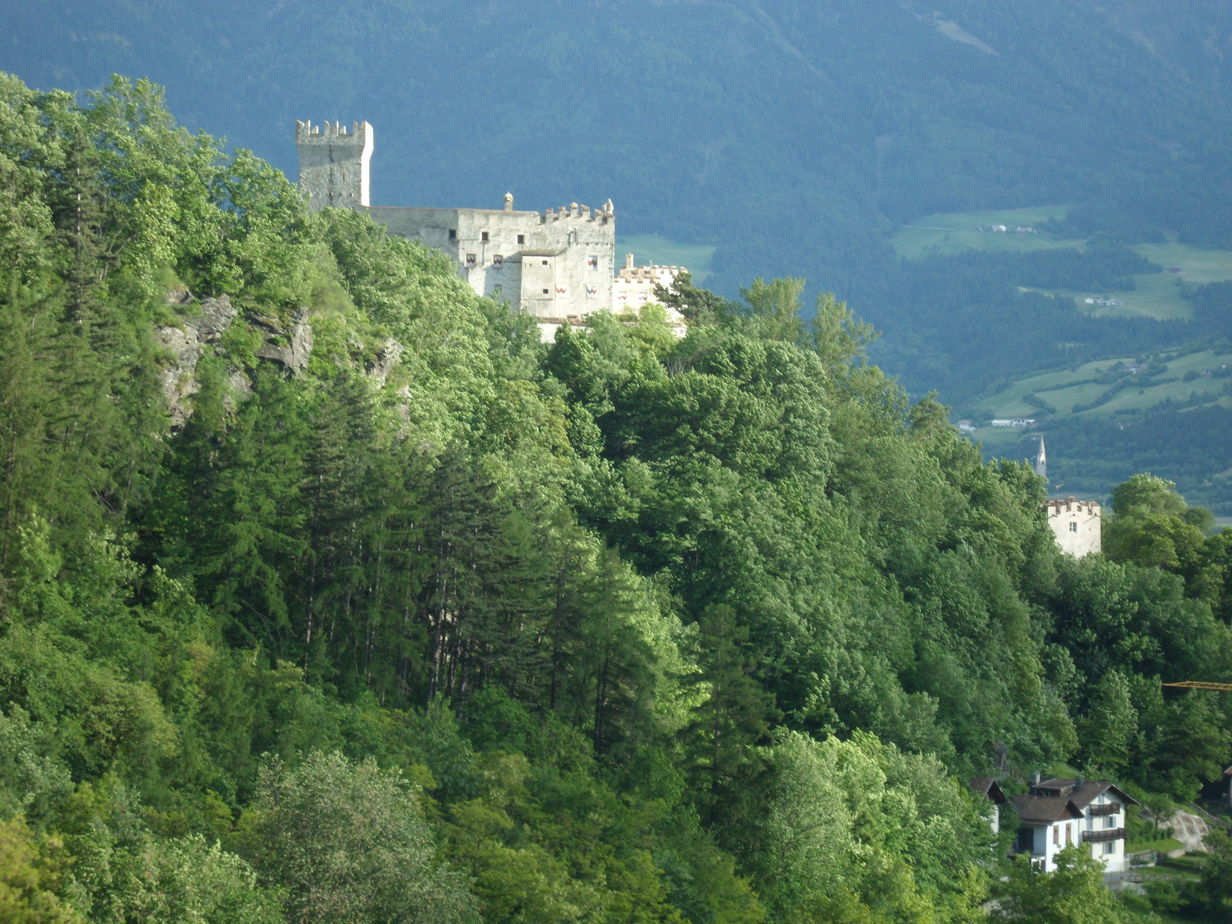 White stone castle with a tall battlemented keep on a wooded hillside