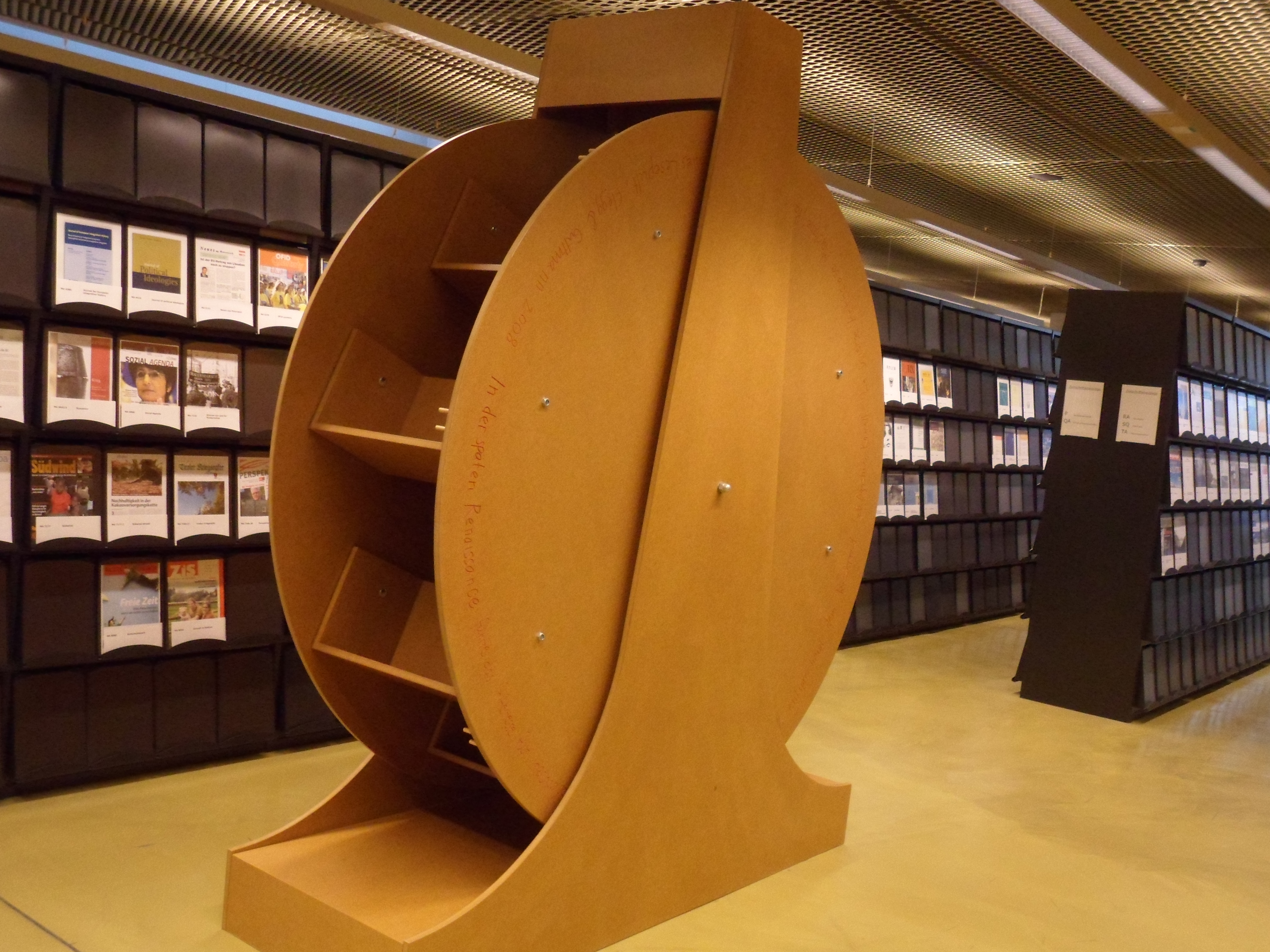 A plywood wheel like a waterwheel with angled bookshelves in place of the buckets