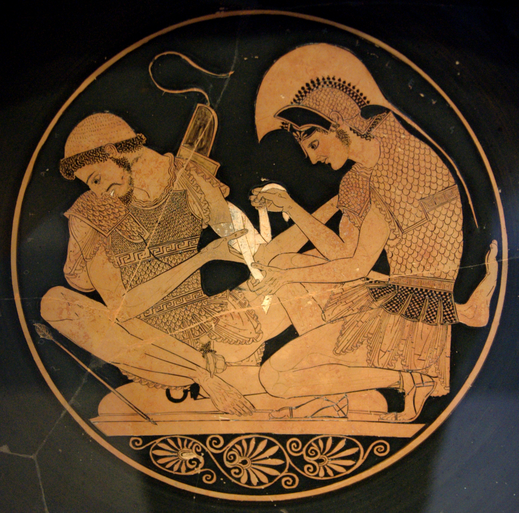 A painting of a circle withing which a man in Greek armour is crouching and bandaging the arm of a second who is sitting on his round shield
