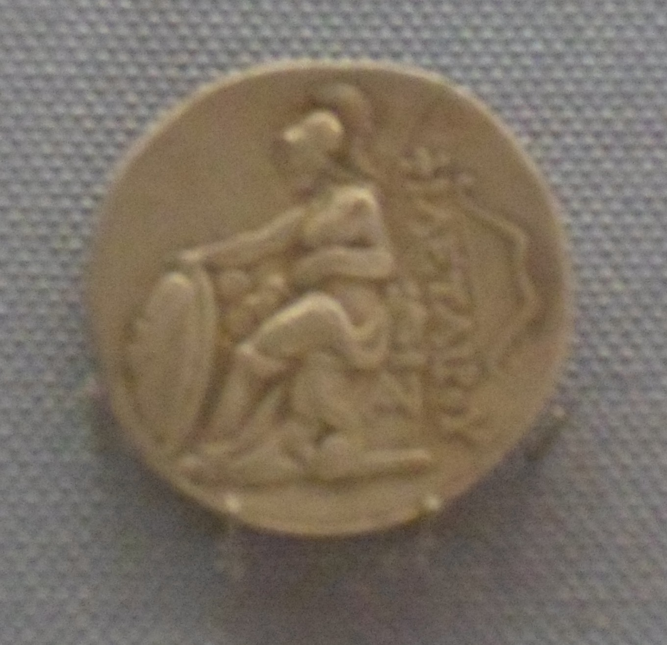 A silver coin with Athena seated on a throne holding a round shield with a word in Greek and a B-shaped bow behind her