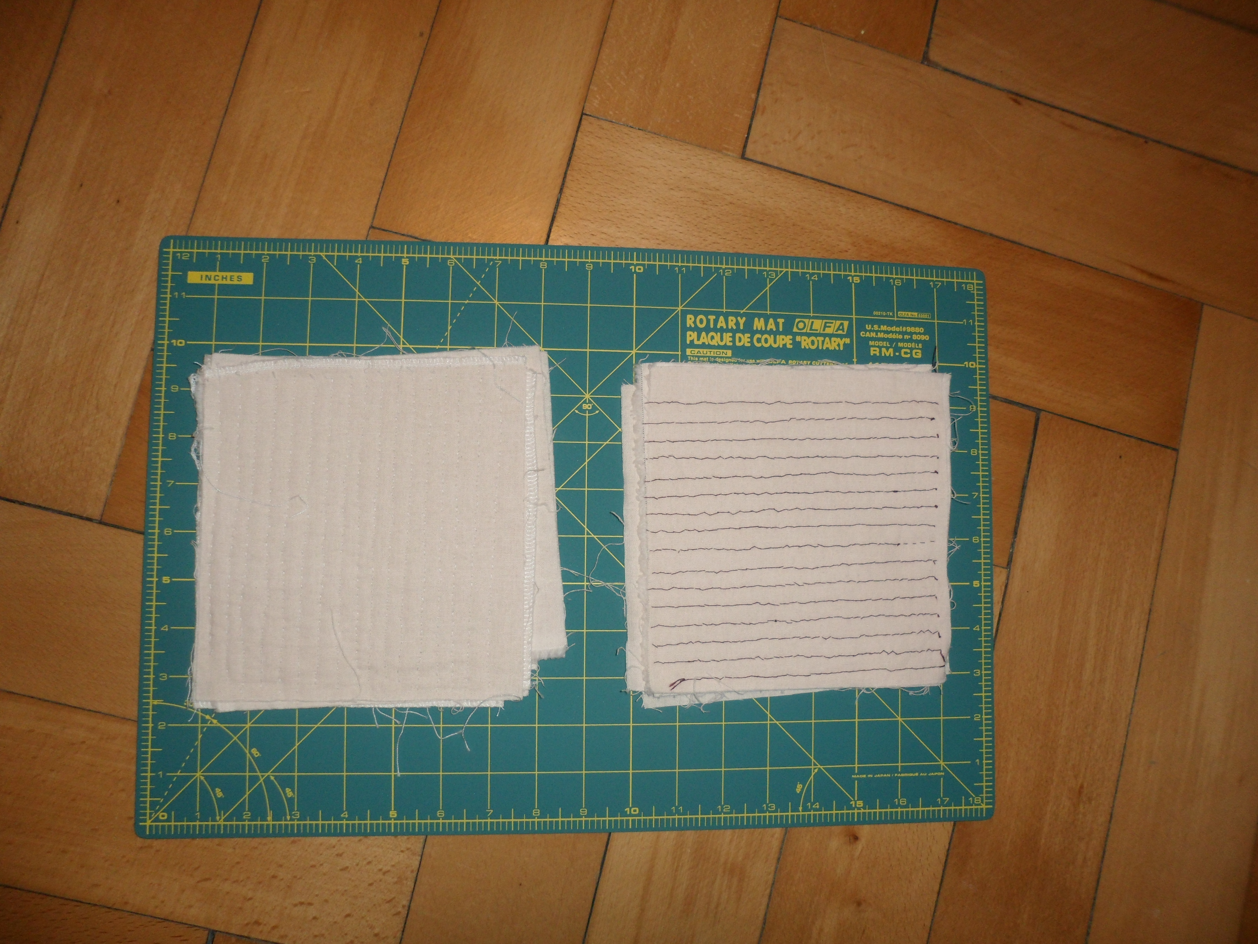 Two 7 inch by 7 inch patches of cloth on a plastic cutting board marked with a grid.  One is quilted vertically every 1 cm with white thread, and one is quilted horizontally every 1 cm with purple thread