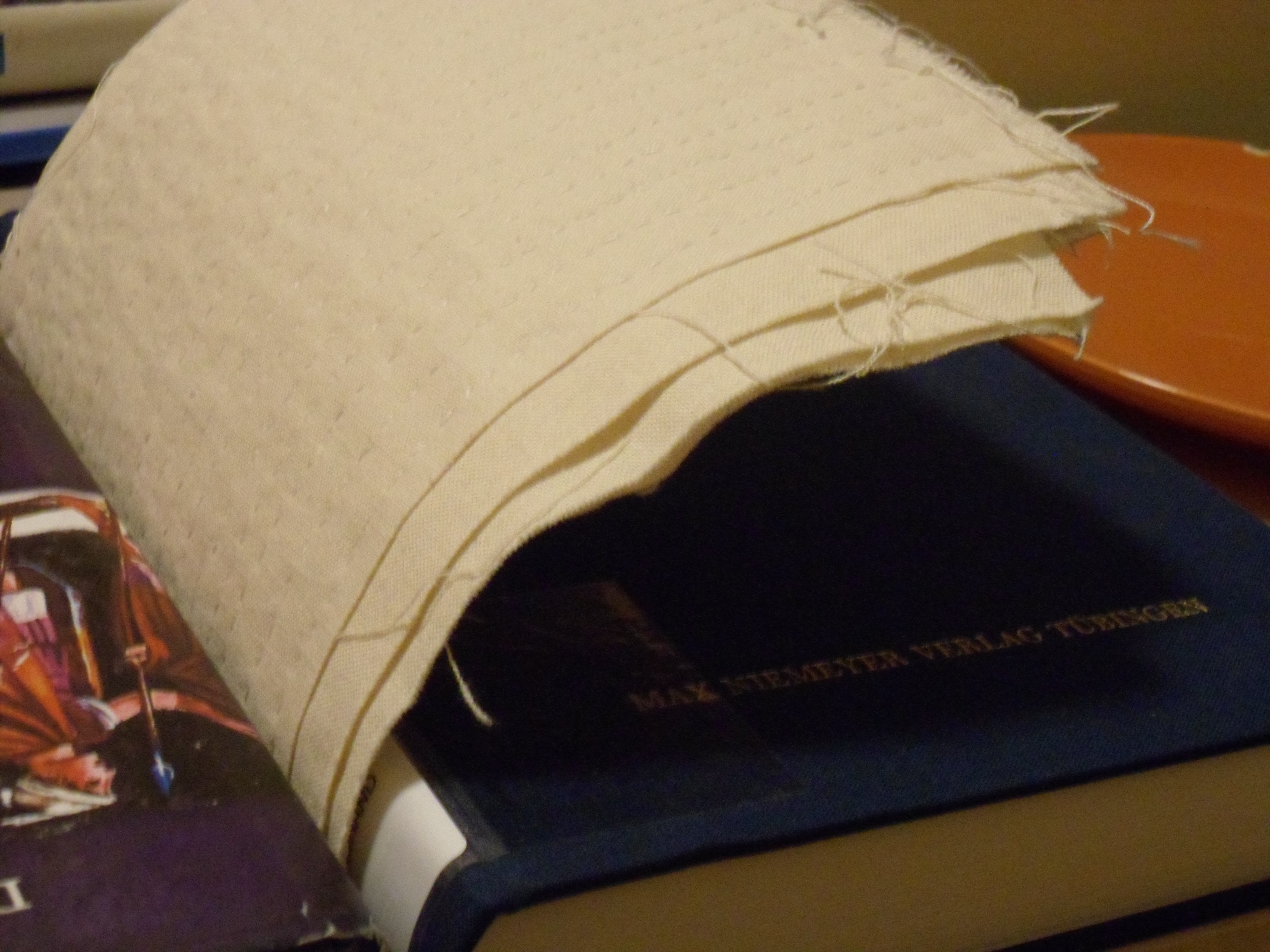 See caption.  The third book has been removed, and the opposite edge is at least a handsbreadth  (7 cm) above the surface of the book beneath it.