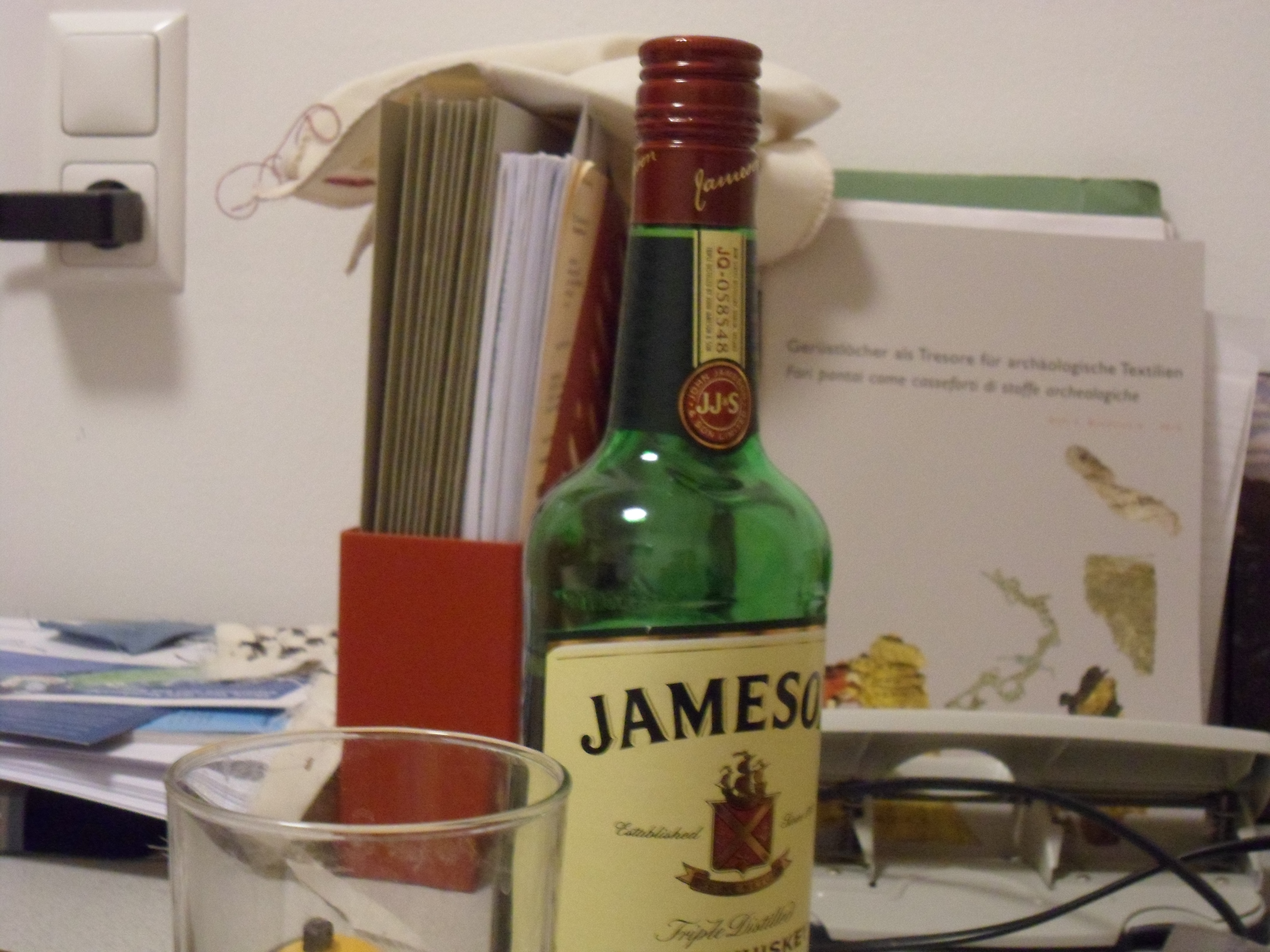 A green glass bottle of whiskey, mostly full, on a cluttered desktop
