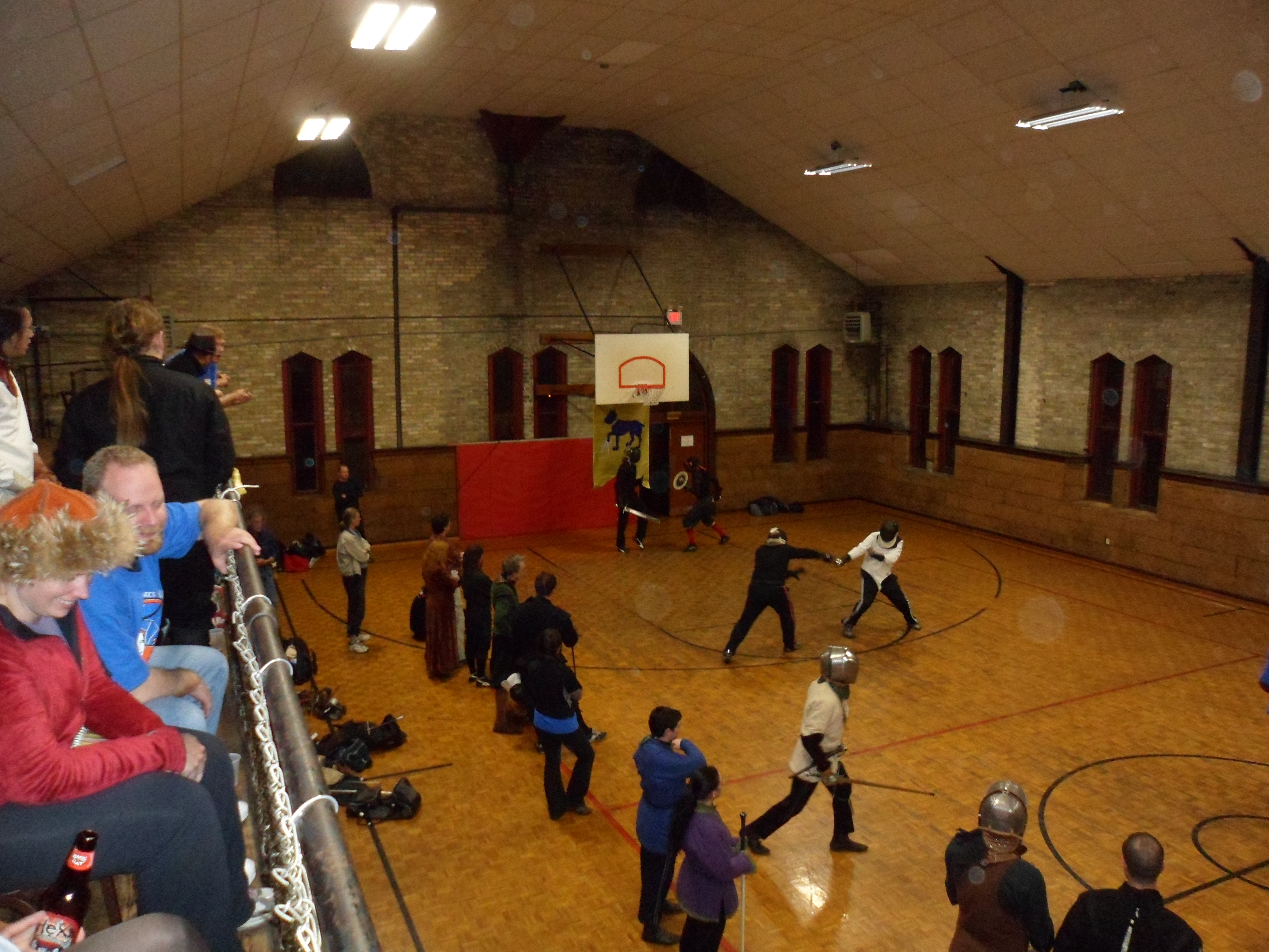 An old parket-floored, stone-walled gymnasium with fencers in diverse styles of clothing from fourteenth-century aketons to 20th-century white fencing jackets