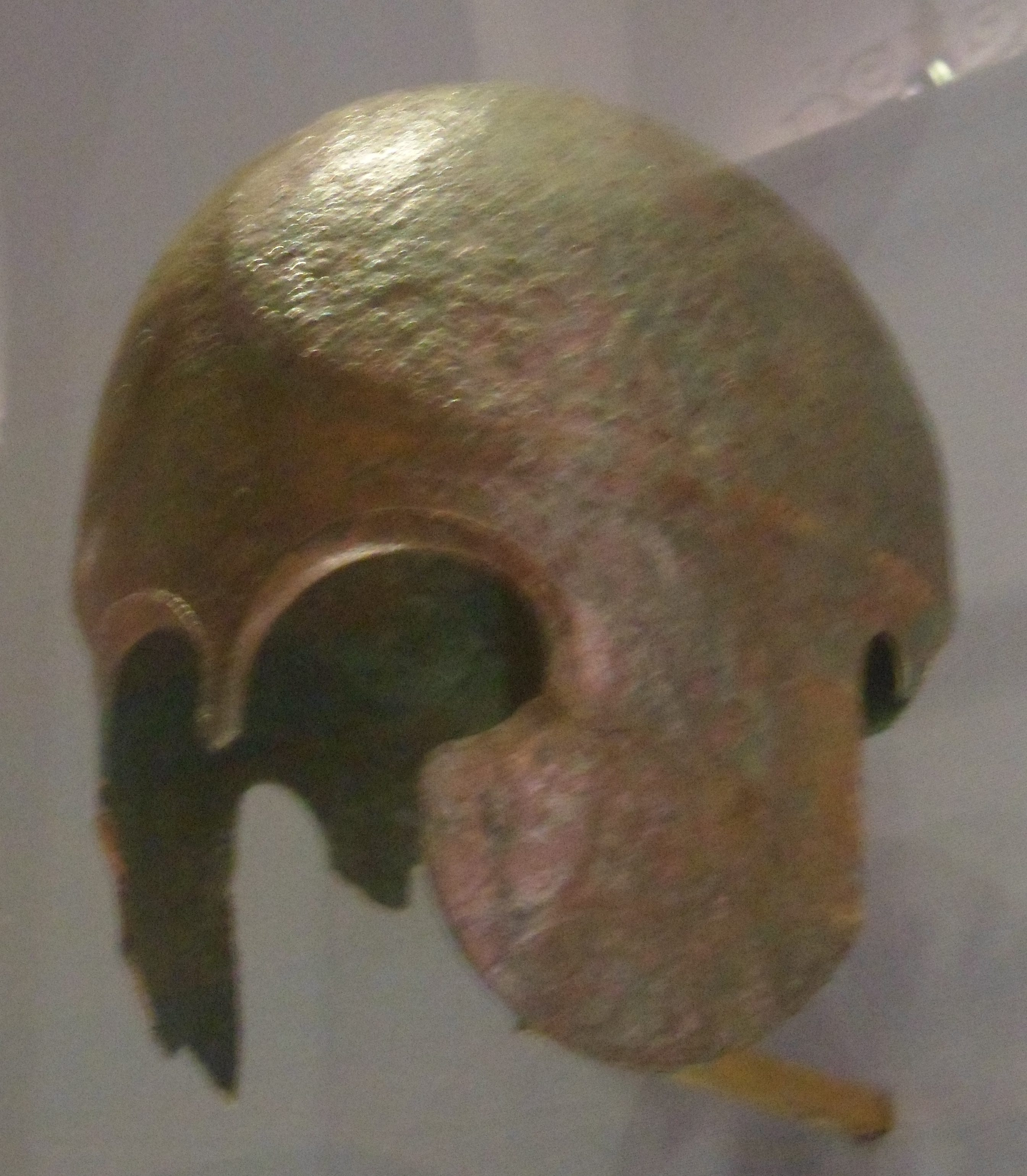 A corroded bronze helmet with cheek flaps and a narrow nasal