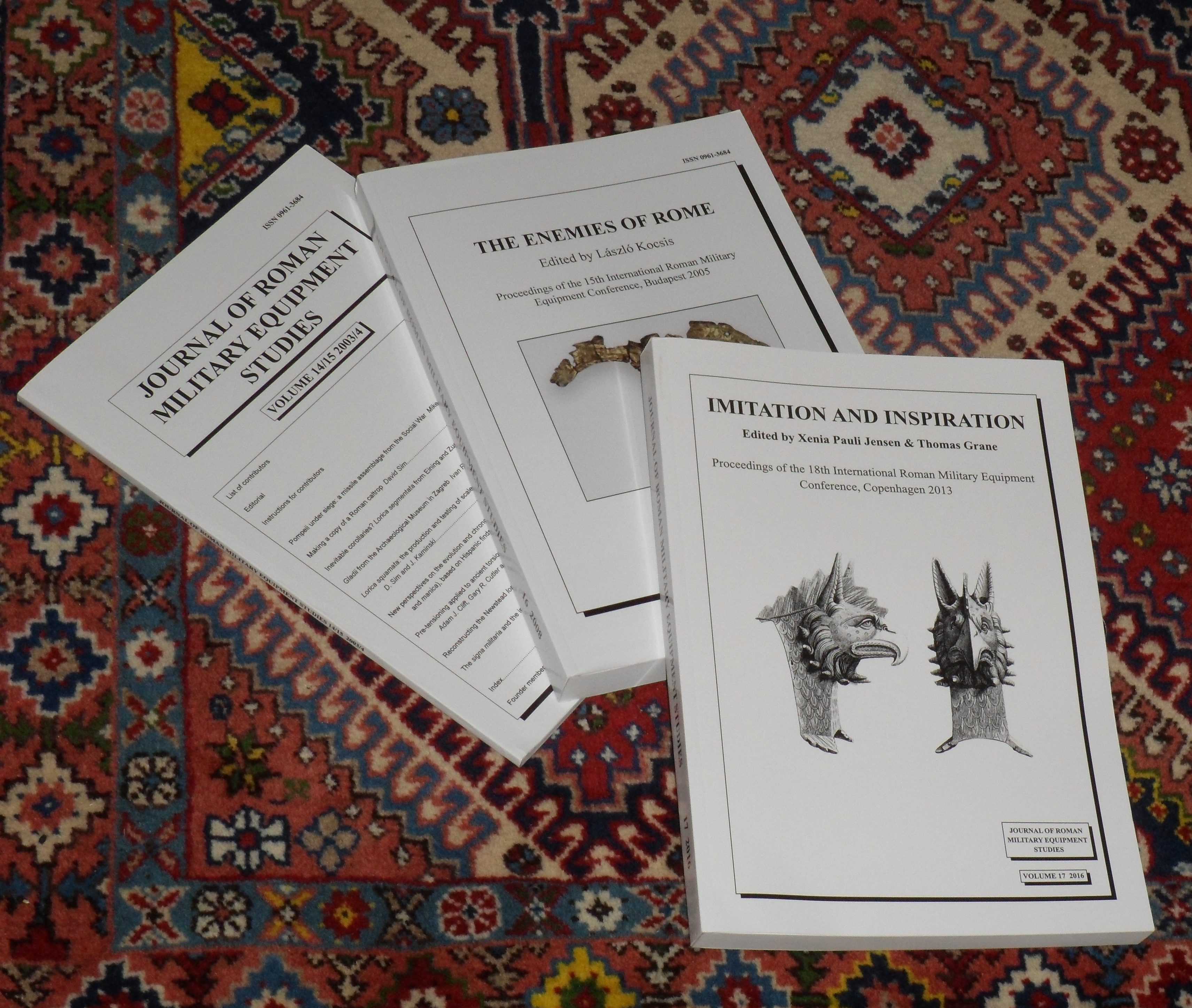Three paper copies a journal scattered across an oriental rug
