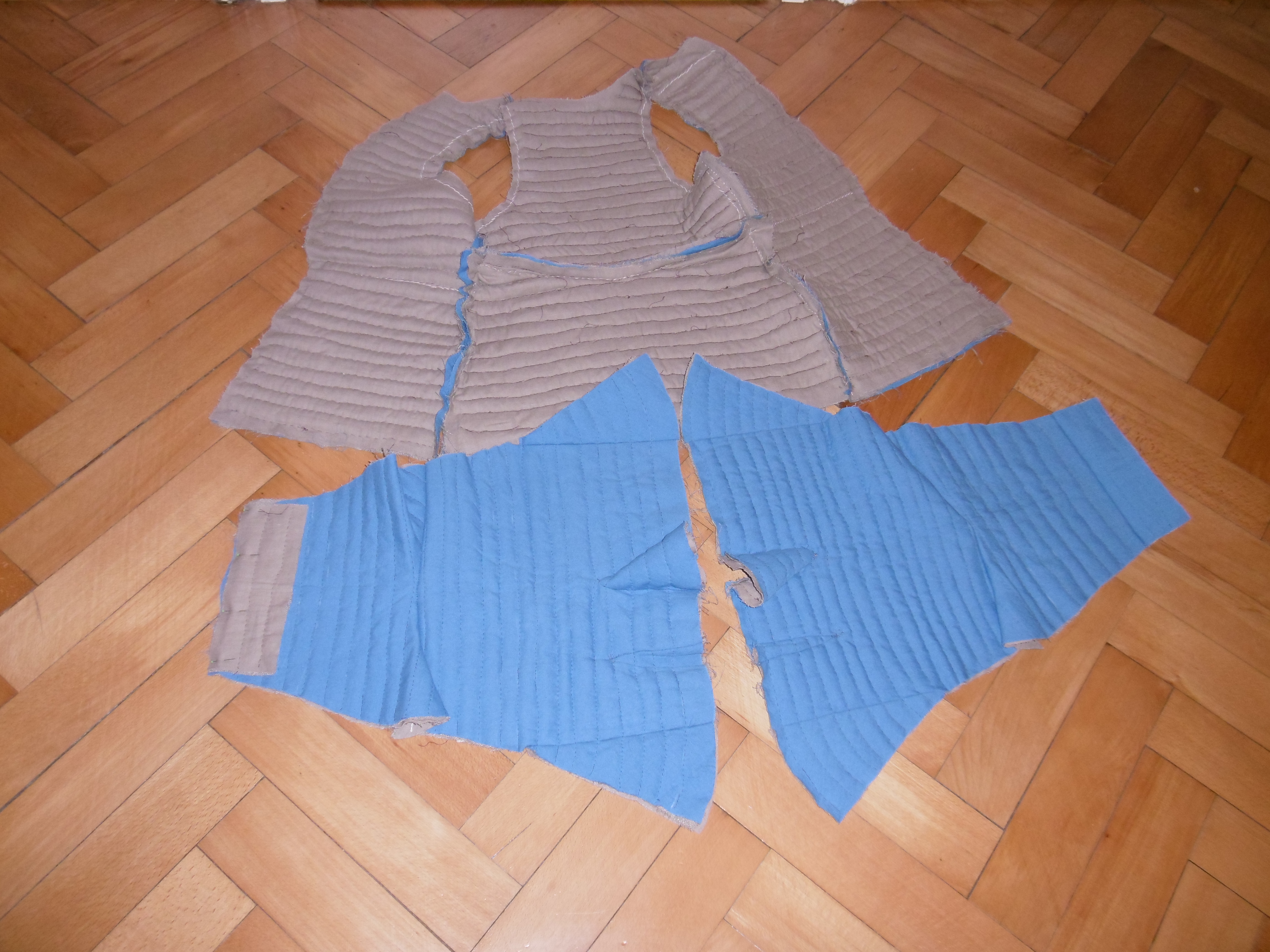 Components of a quilted doublet spread on the floor showing all parts assembled with the proper layers inside and outside