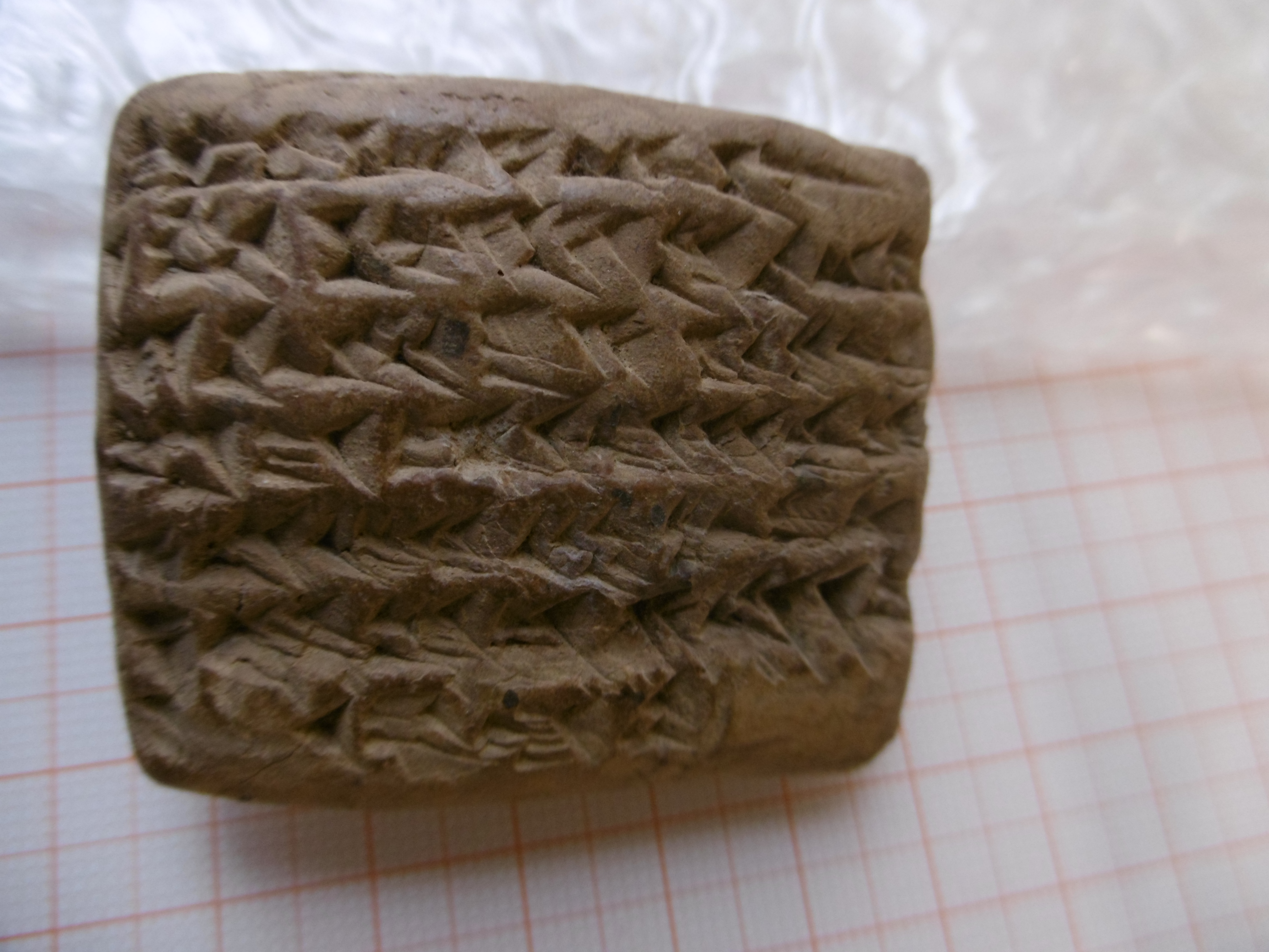 A photograph of a cuneiform tablet against the backdrop of graph-paper and bubble-wrap