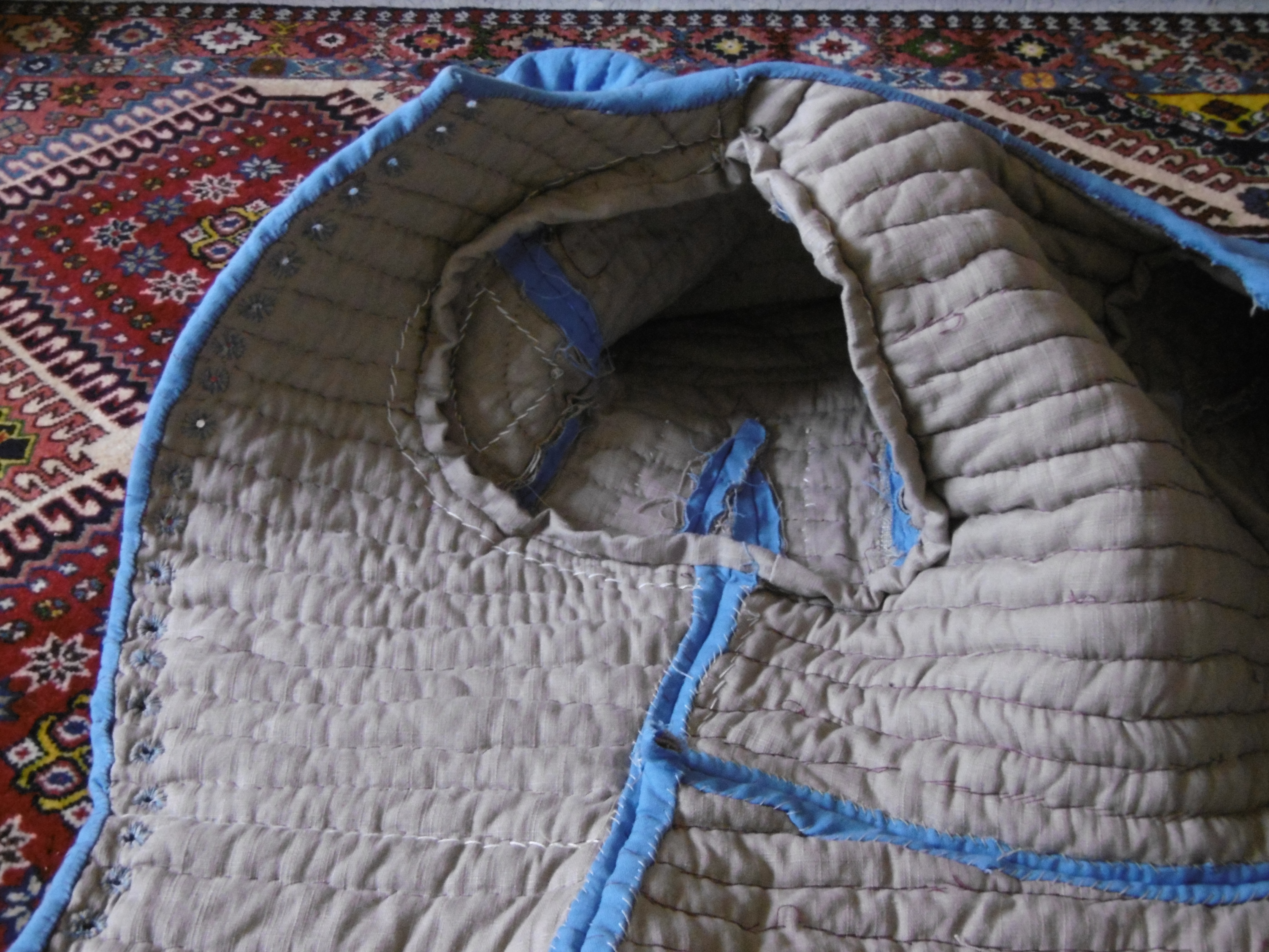 A quilted garment against the background of a carpet
