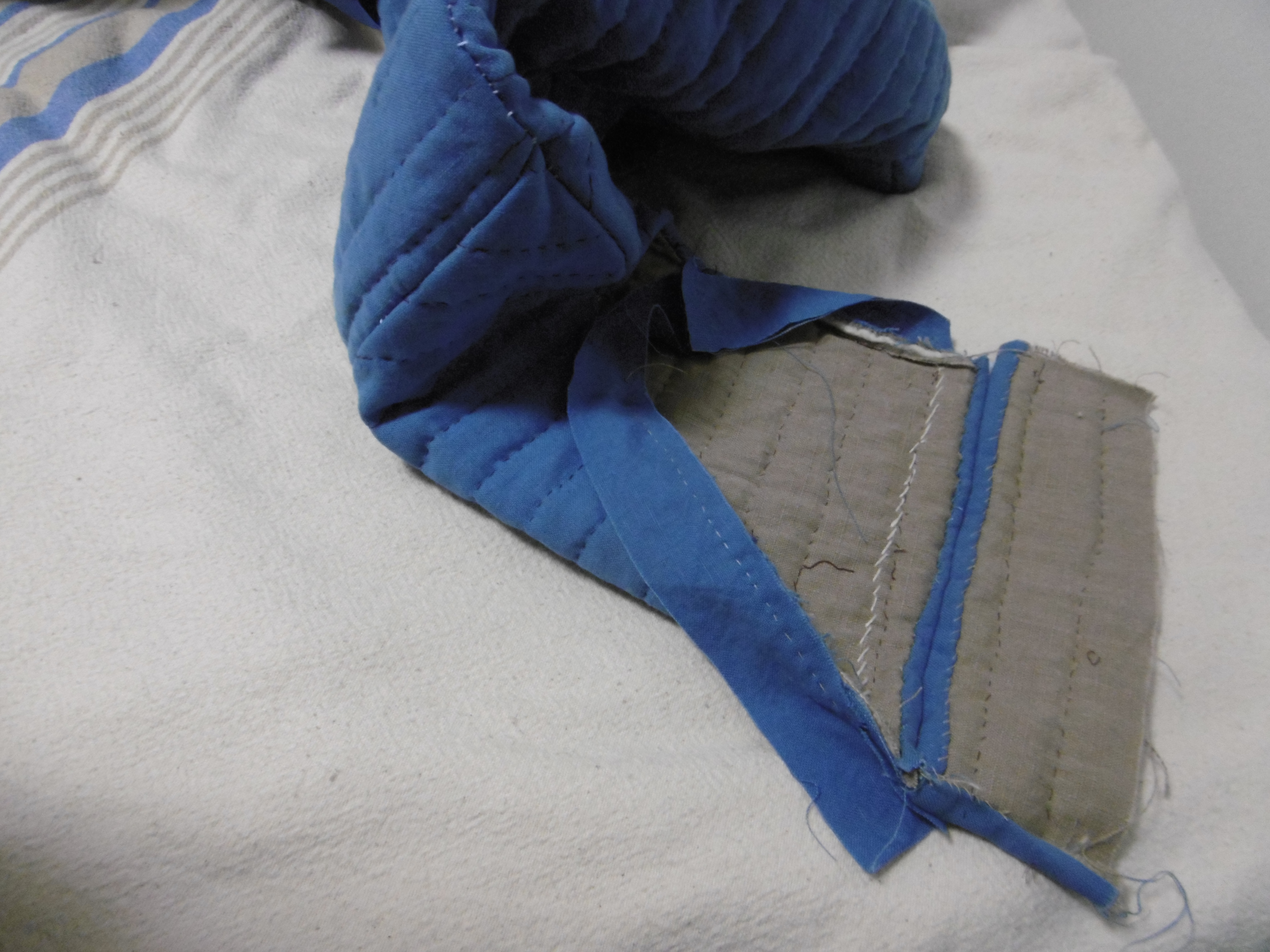 The unfinished end of the sleeve of a quilted garment against a cloth background