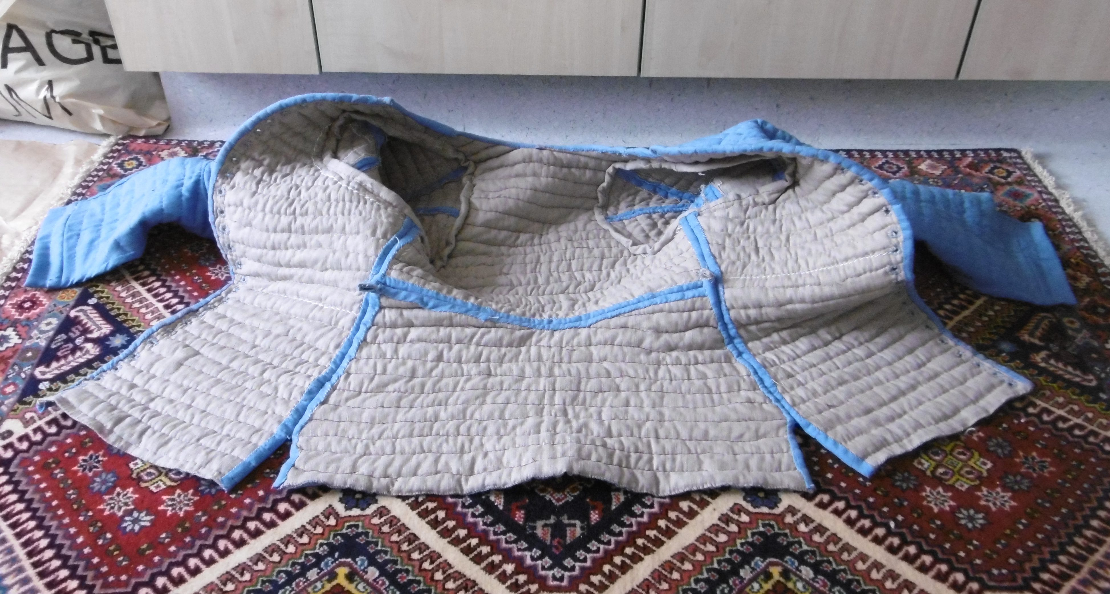 A quilted garment spread open on a carpet