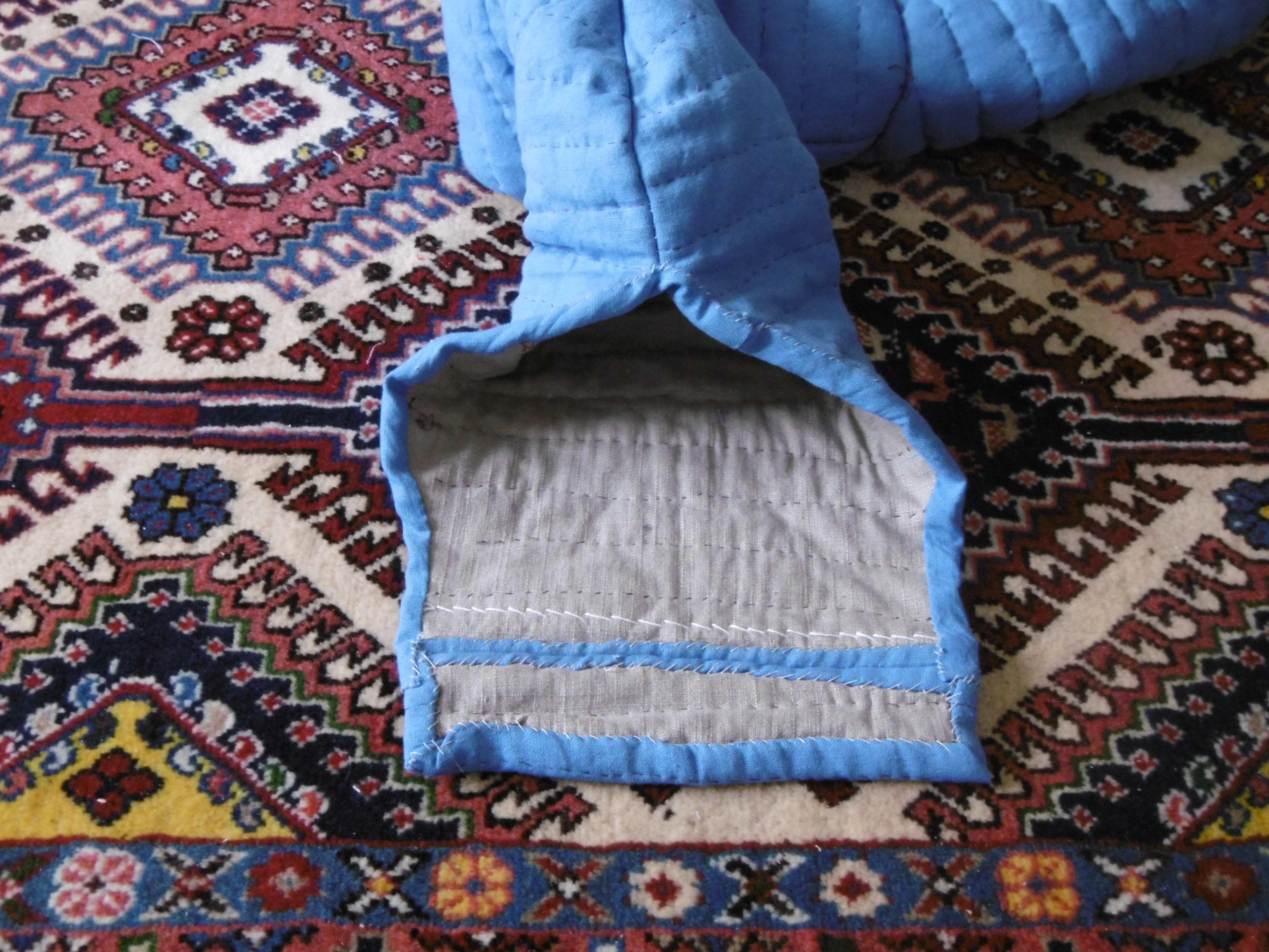 The finished sleeve of a quilted garment against the background of a carpet