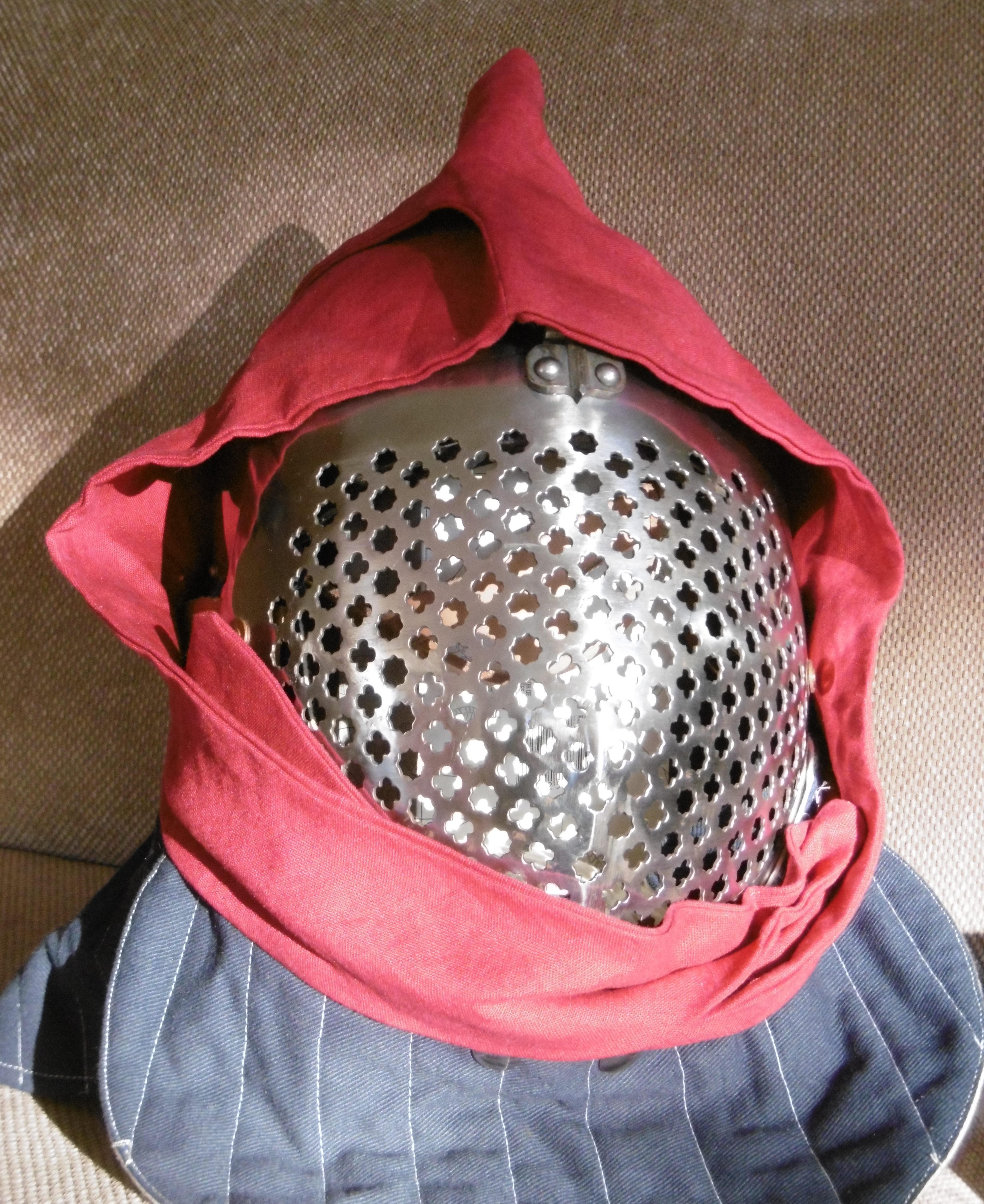 A bascinet with a perforated-metal visor wearing a red hood with cheek flaps and a tall comb at the top folded down