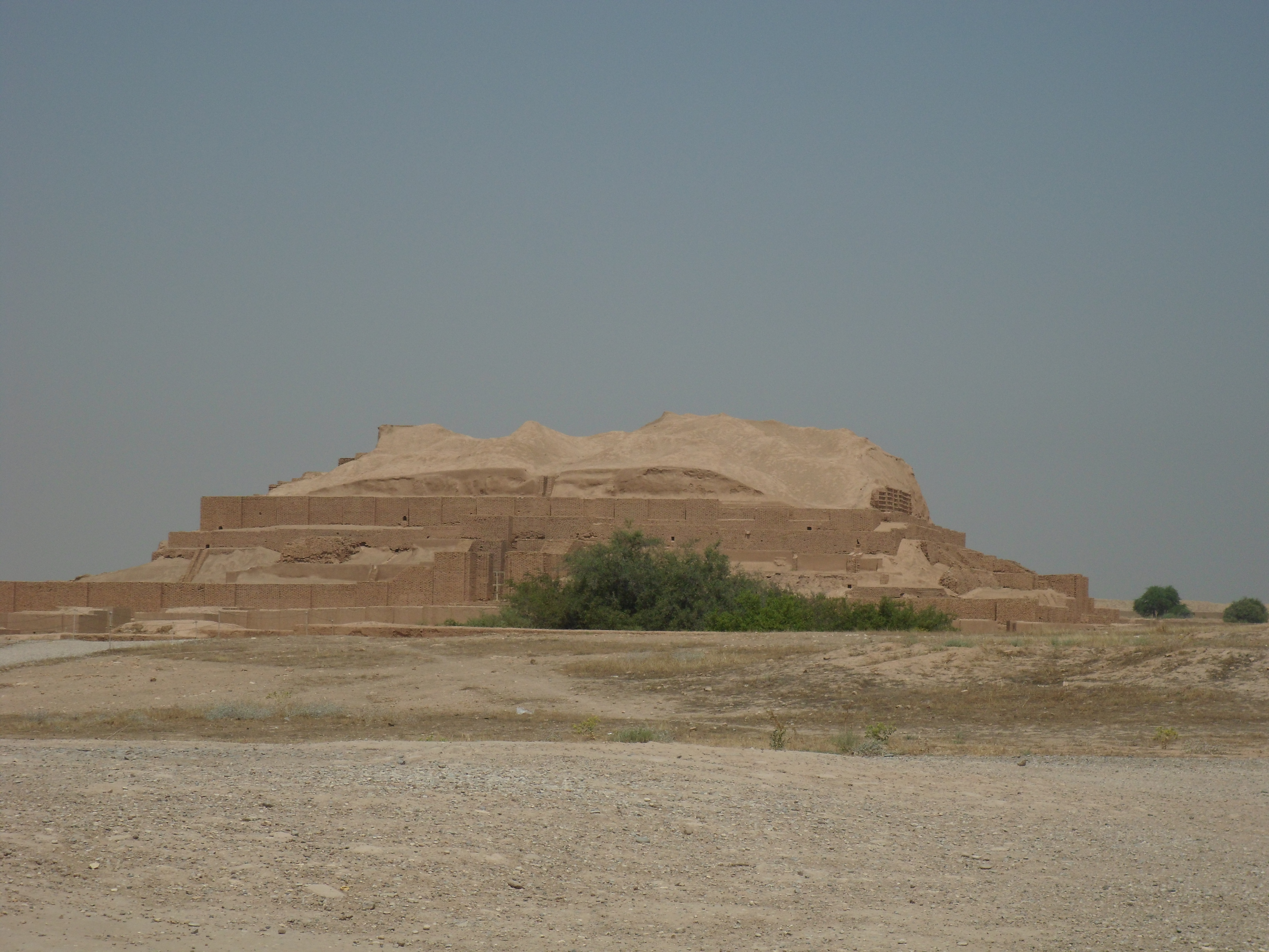 An eroded ziggurat against the background of the blue sky with bushes and depressions in the foreground