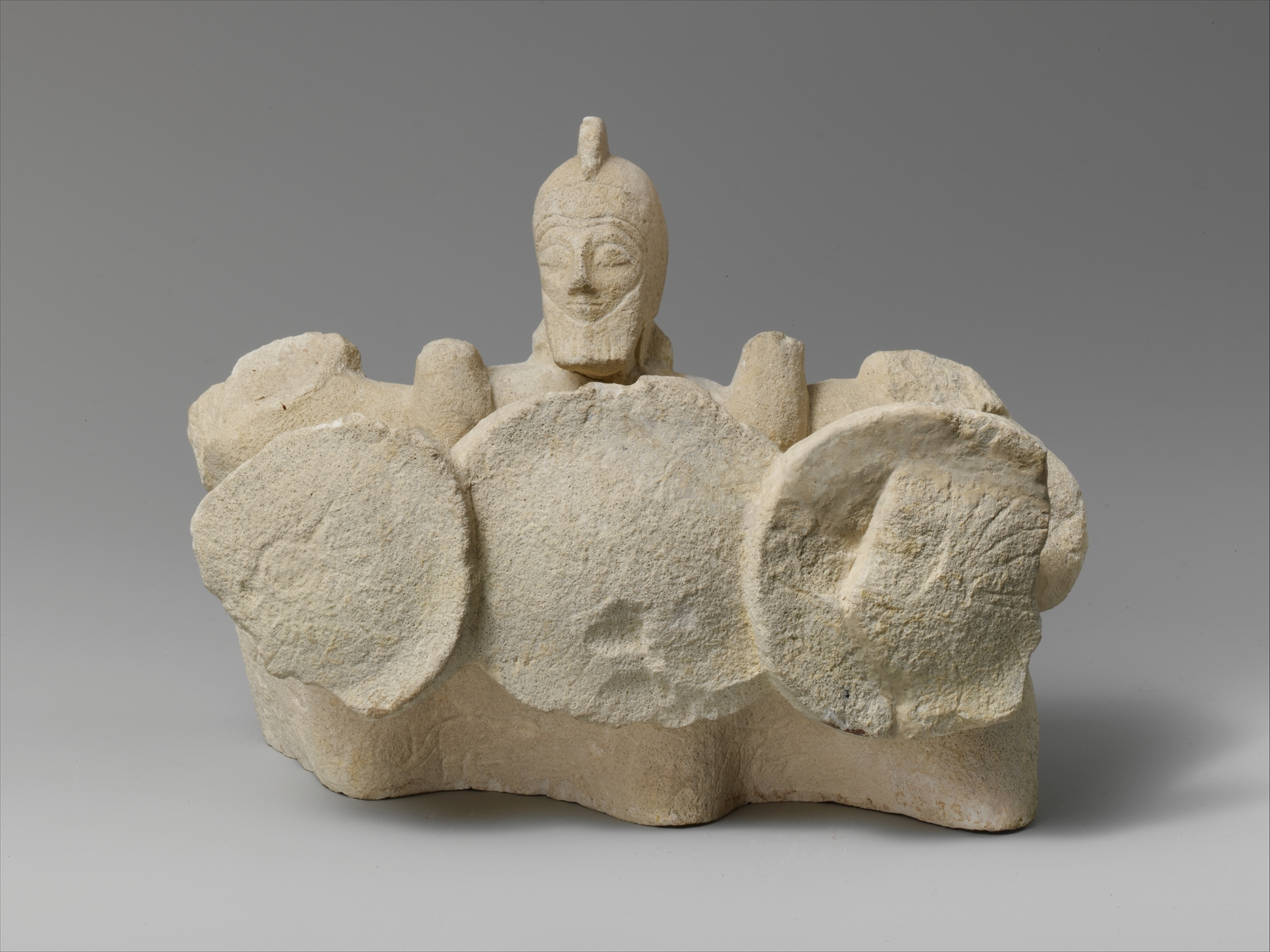A battered statue of three men forming a shield wall with round domed shields