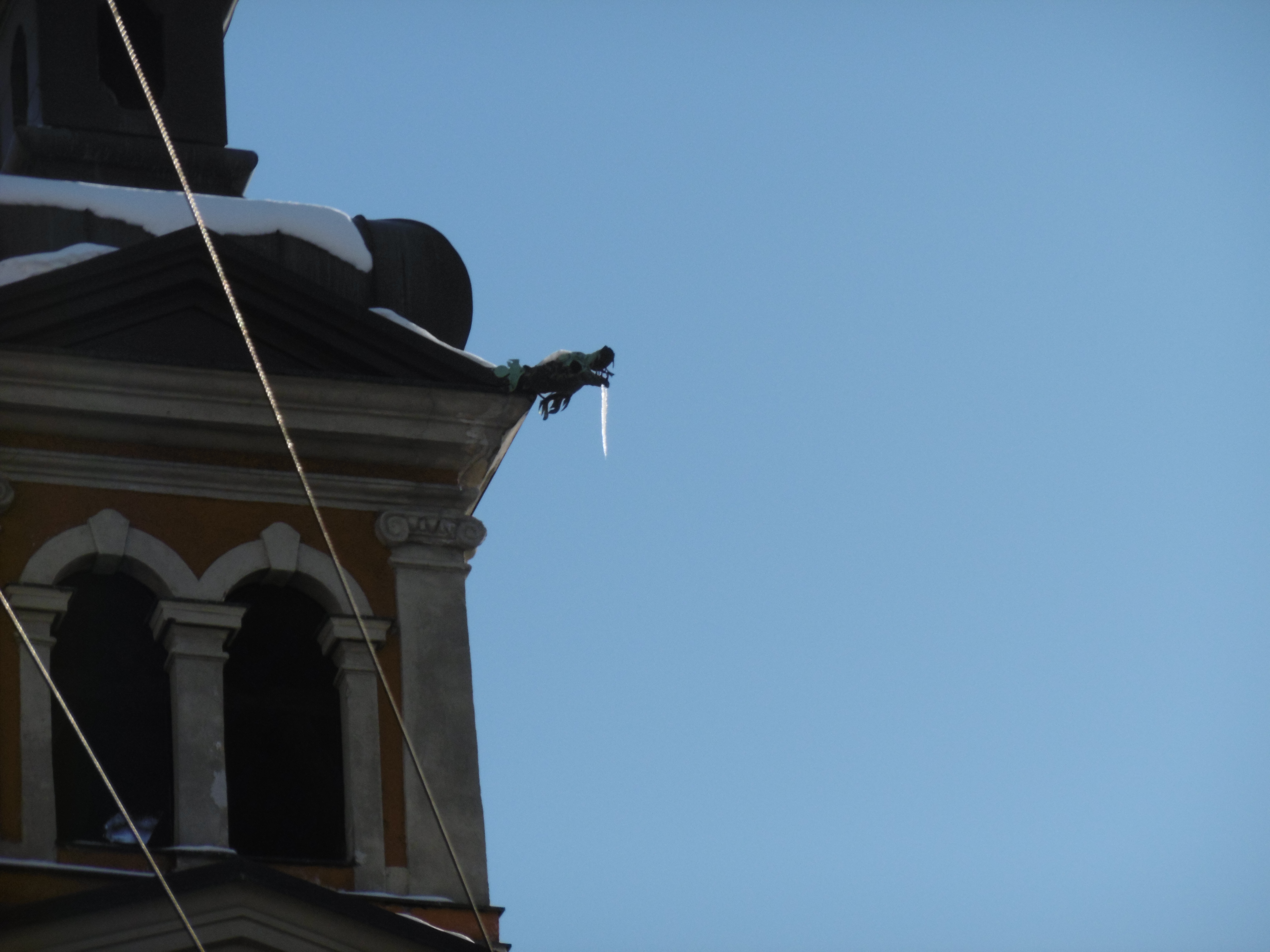 A copper rainspout with an icicle hanging from its mouth