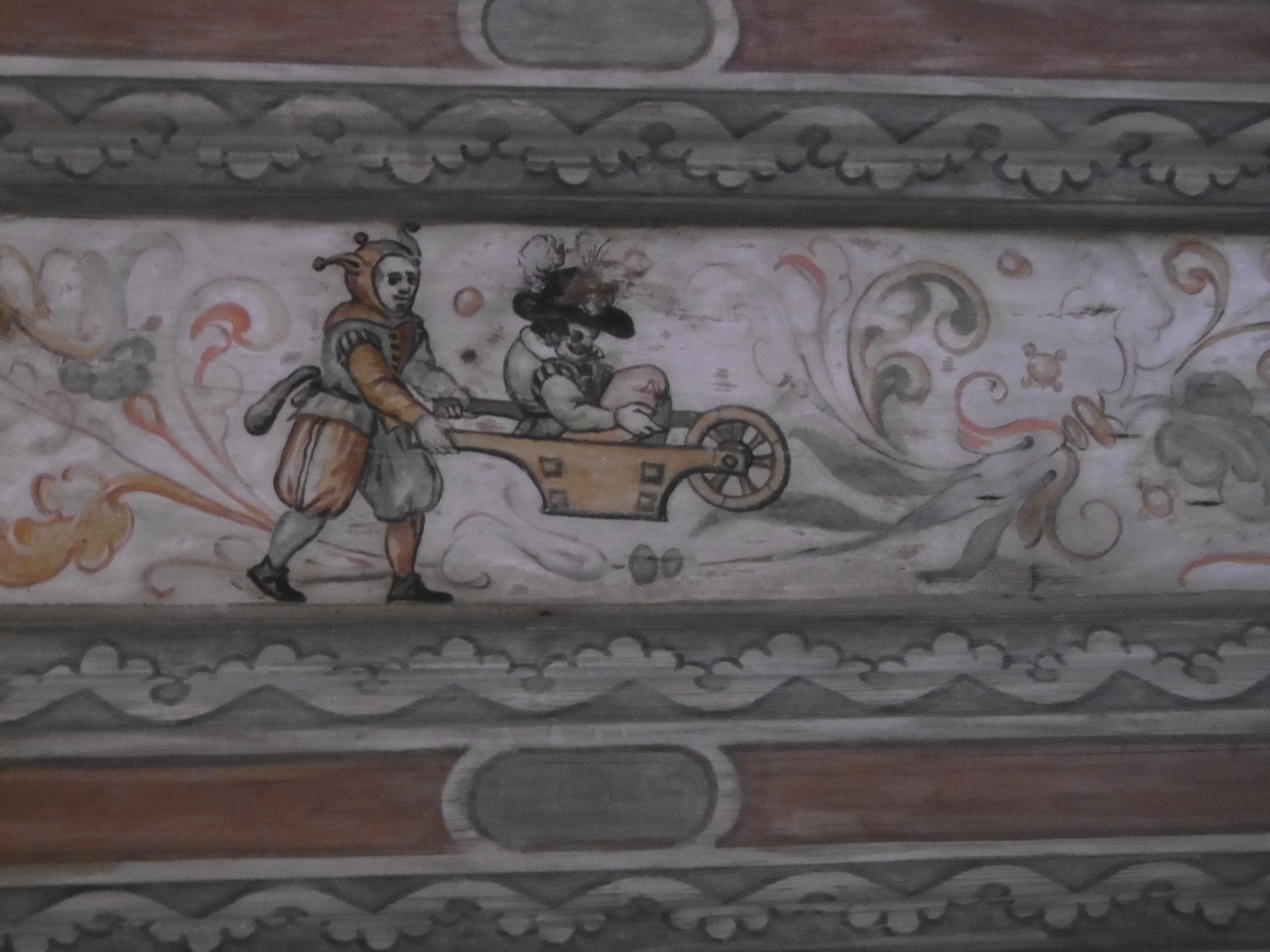 A painting of a fool in red and green mi-parti wheeling a man wearing an extravagant plumed hat in a wheelbarrow