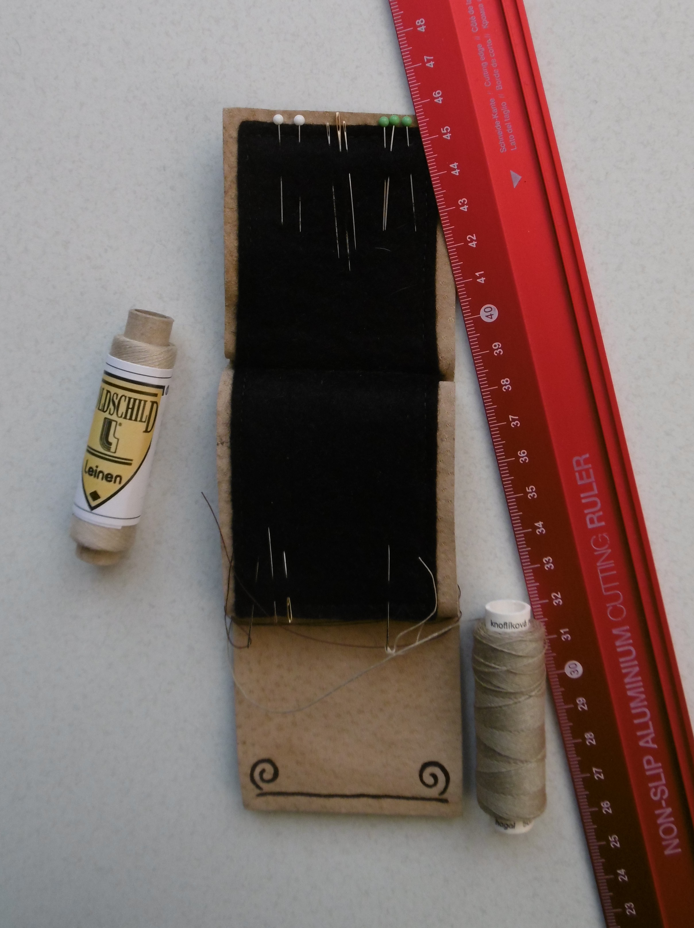 A case for pins and needles consisting of a flat piece of leather lined with felt