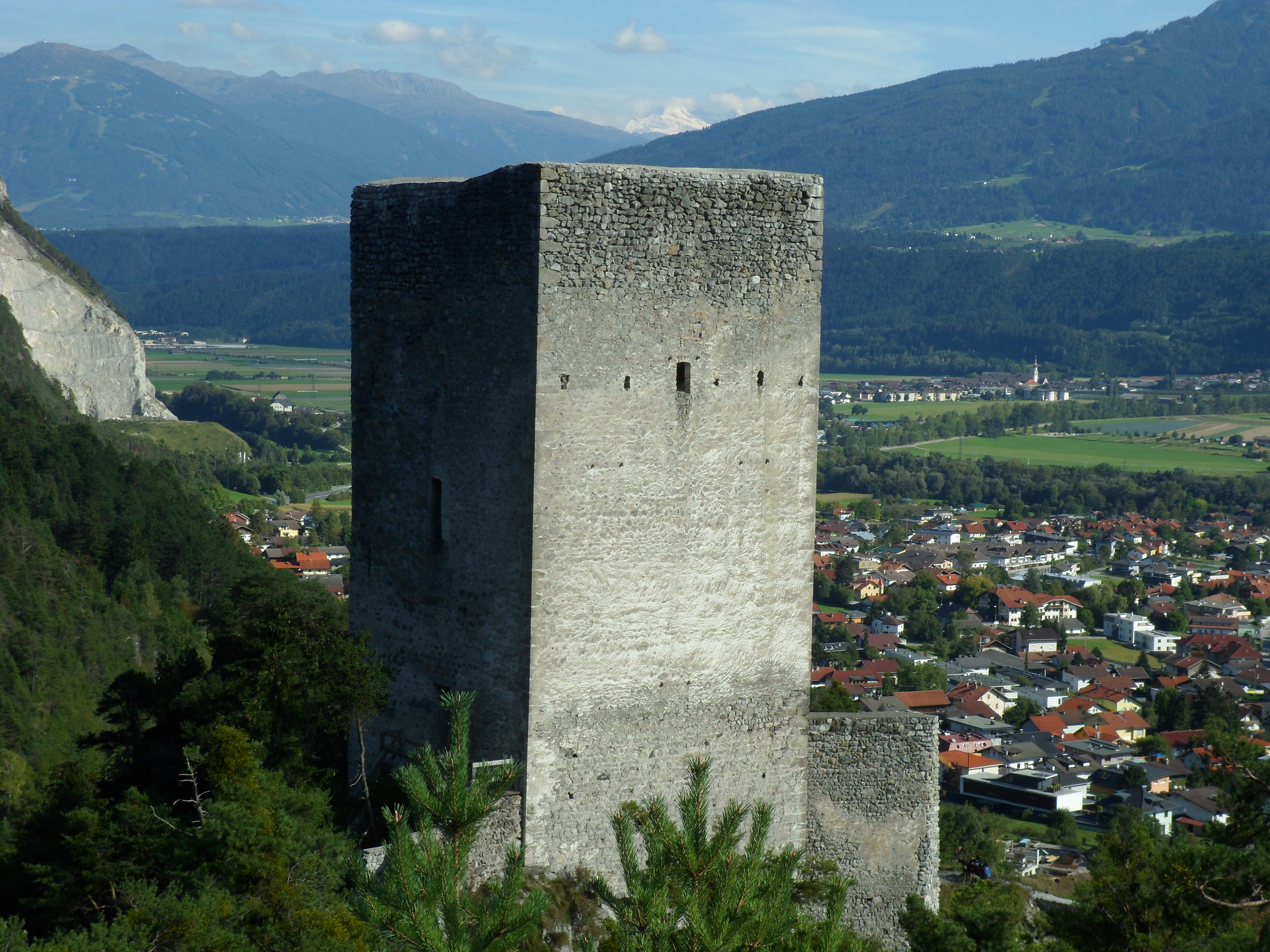 A photo of the bare stone keep of a cliff-top castle overlooking a small town