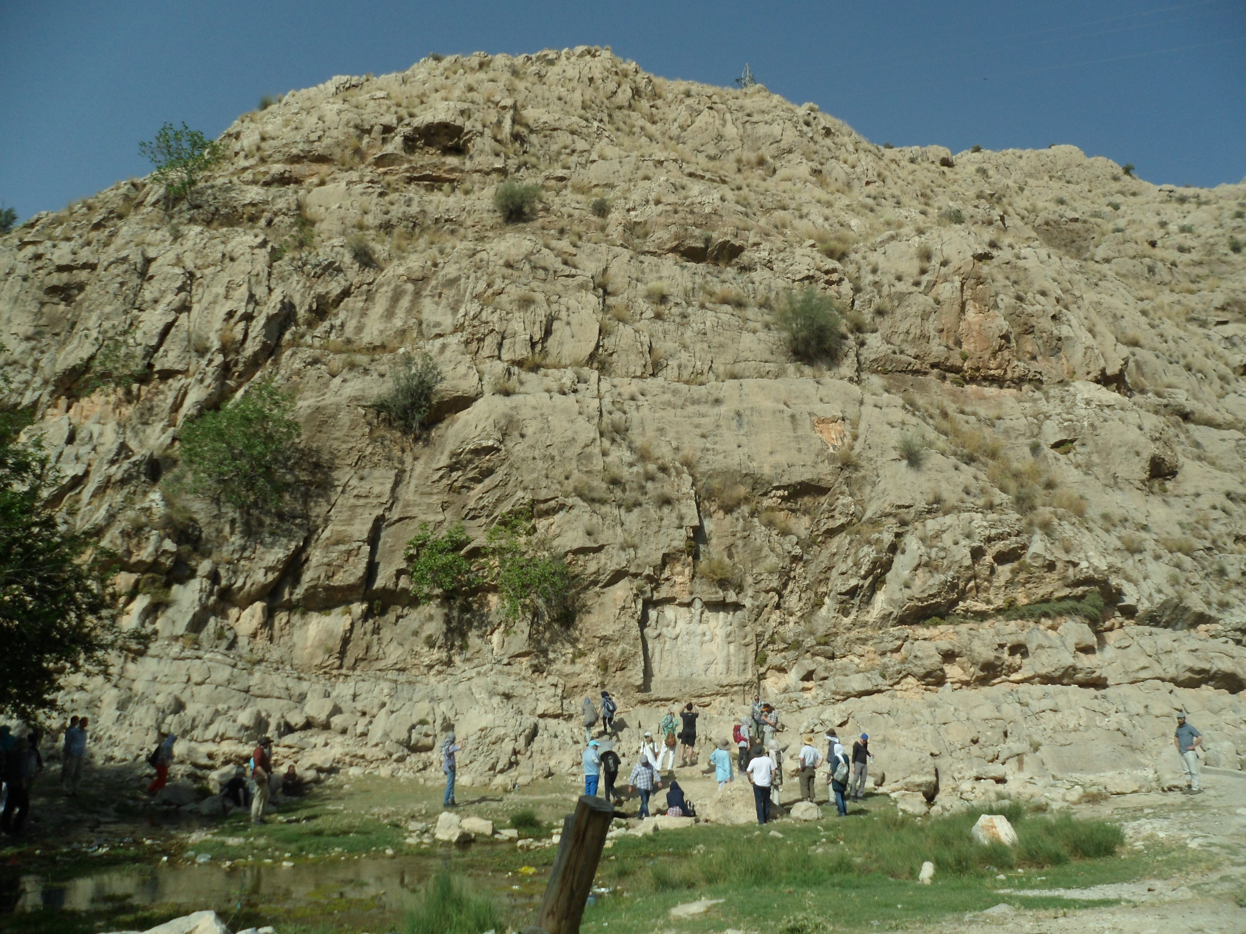 A relief of an enthroned king carved into a cliff over a natural spring