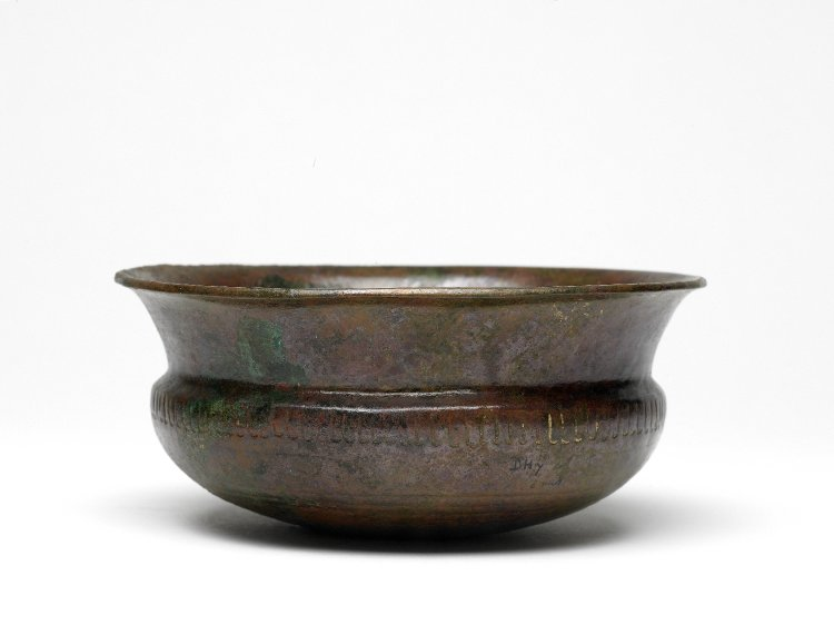 A shallow bowl of beaten copper with a floral motif engraved around the middle