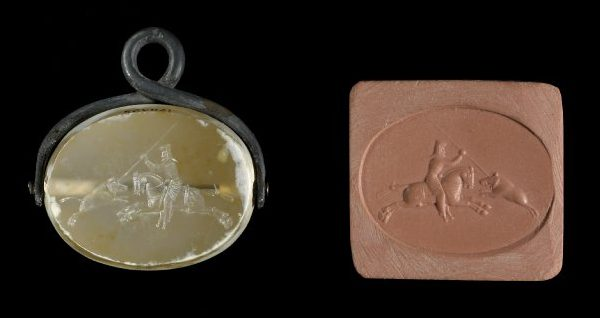 An oblong sealstone showing a horseman stabbing a charging boar with a lance