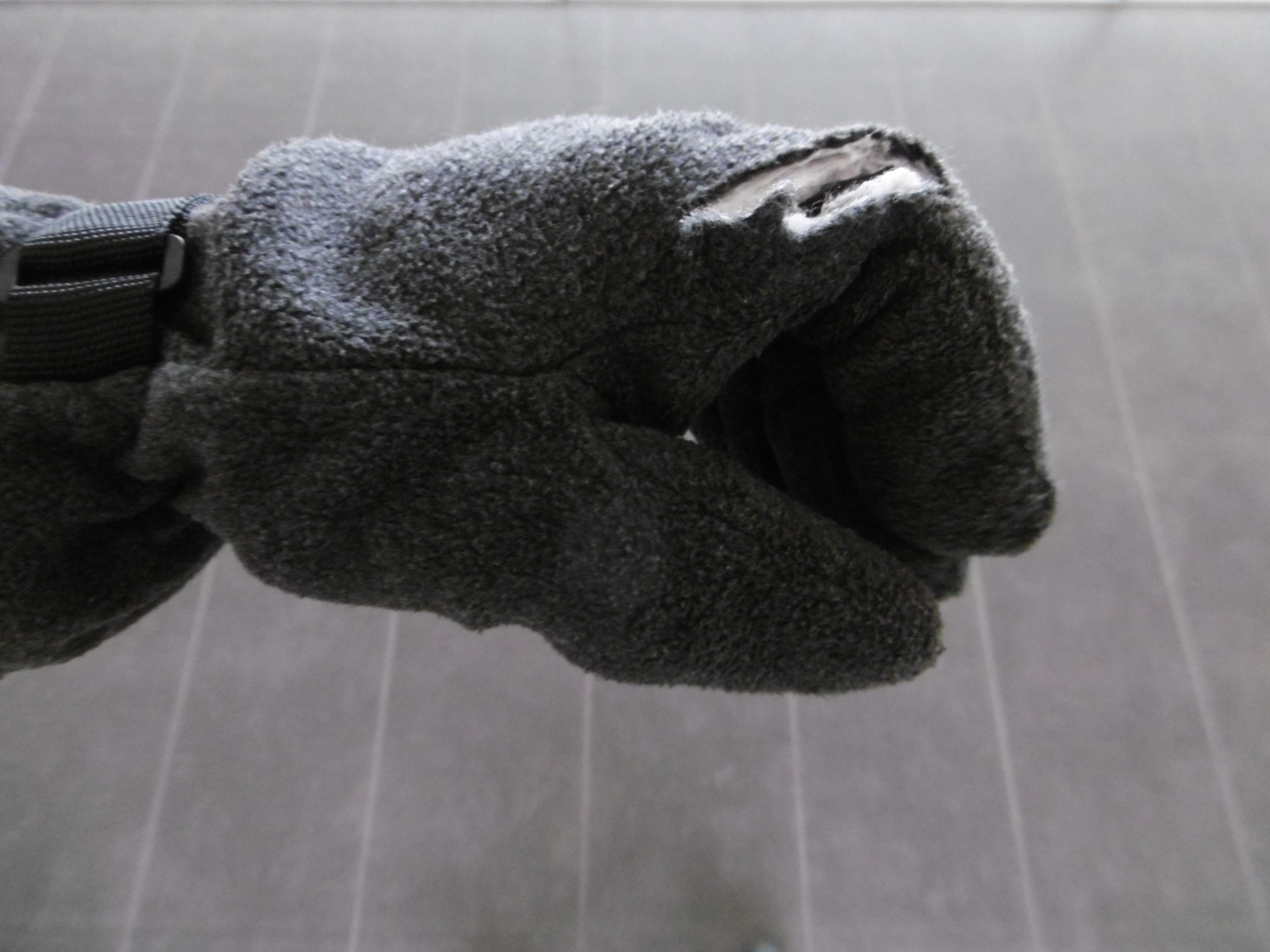 Fleece gloves with a cut through one finger from a cyclist ramming into the wearer