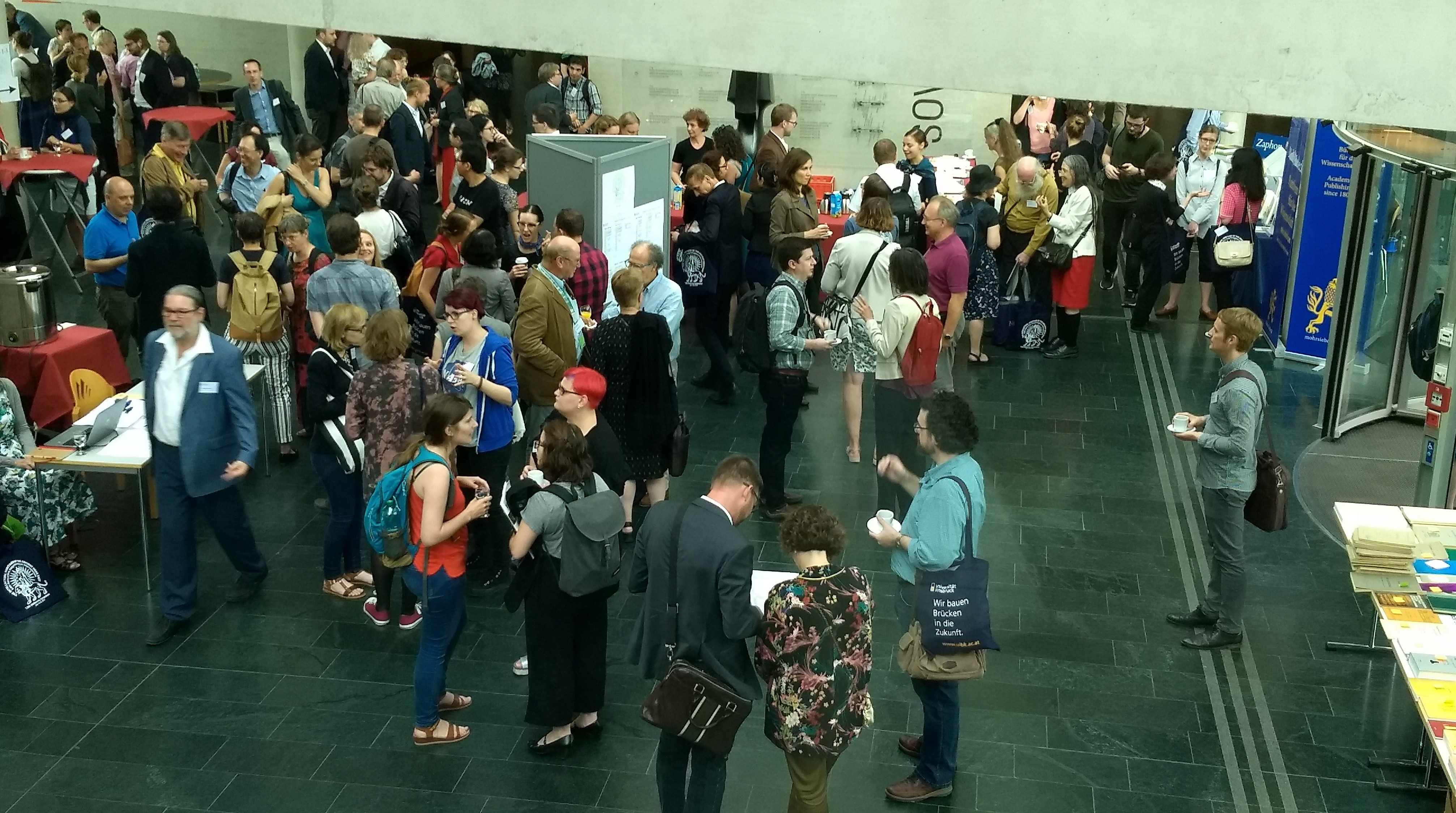 A crowd at an academic conference in a lobby with a stone floor, concrete walls, and several tables of books, snacks, and registration papers