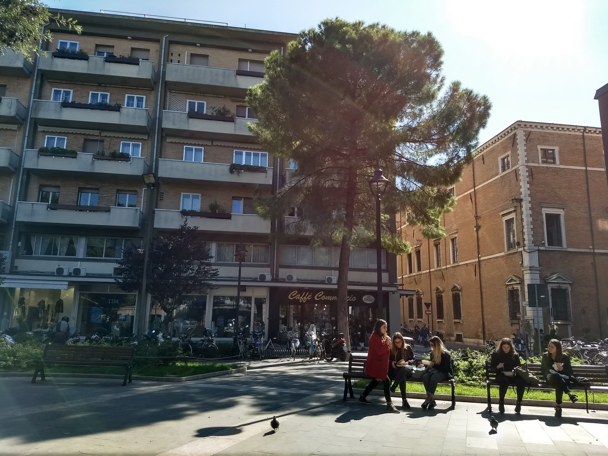 A square with trees, modern apartment buildings, old brick buildings, and young people talking and sitting on benches