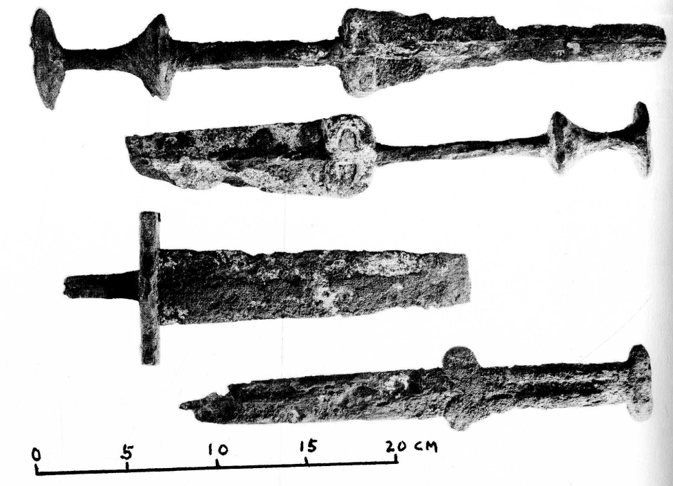 Two rusty daggers with pommels shaped like a toy top, a rusty cross-hilted sword with a broken blade,and a rusty dagger with a two-lobed crossguard