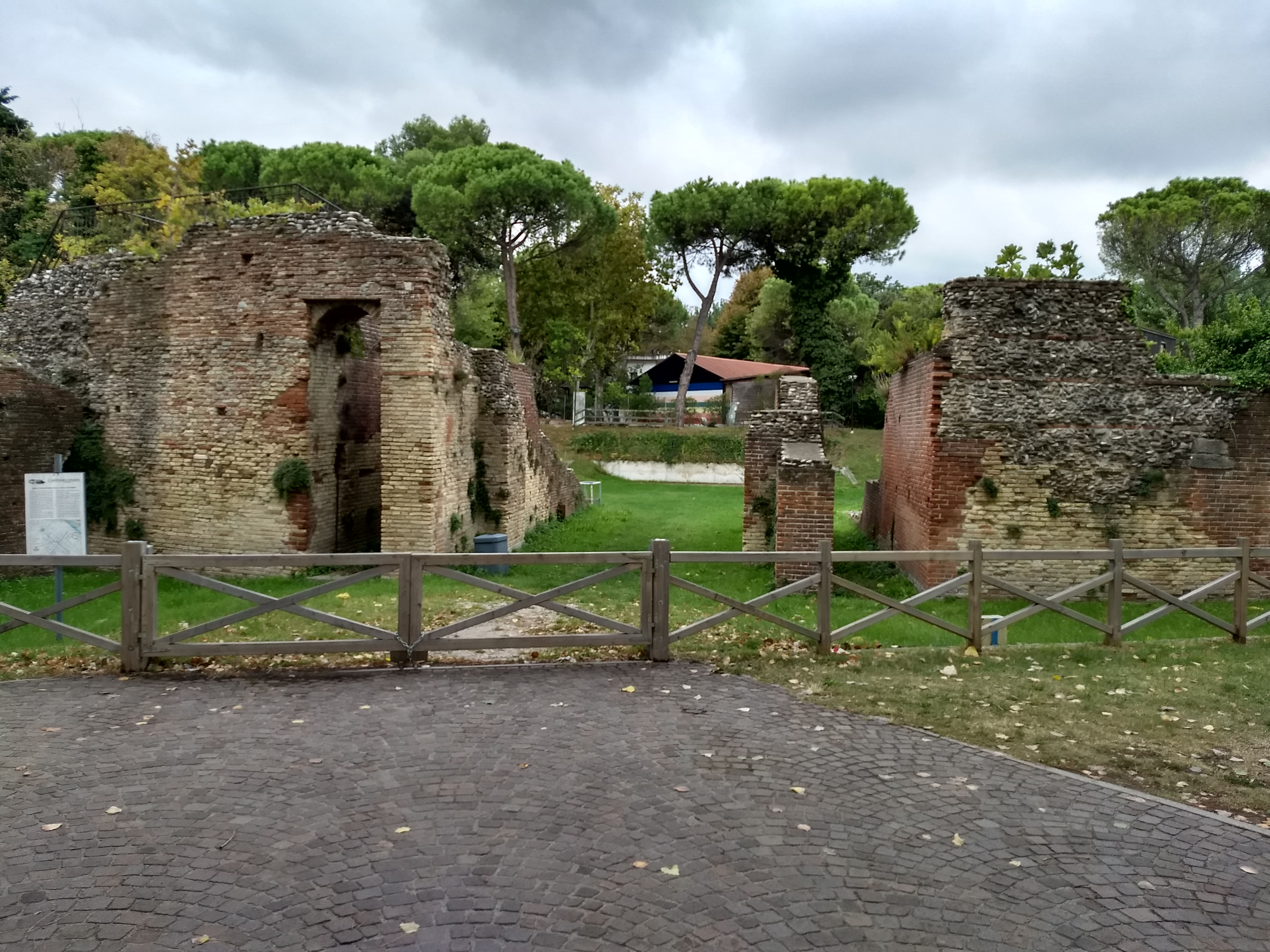 The ruins of a brick-and-concrete structure in a grassy pit with trees and houses in the background