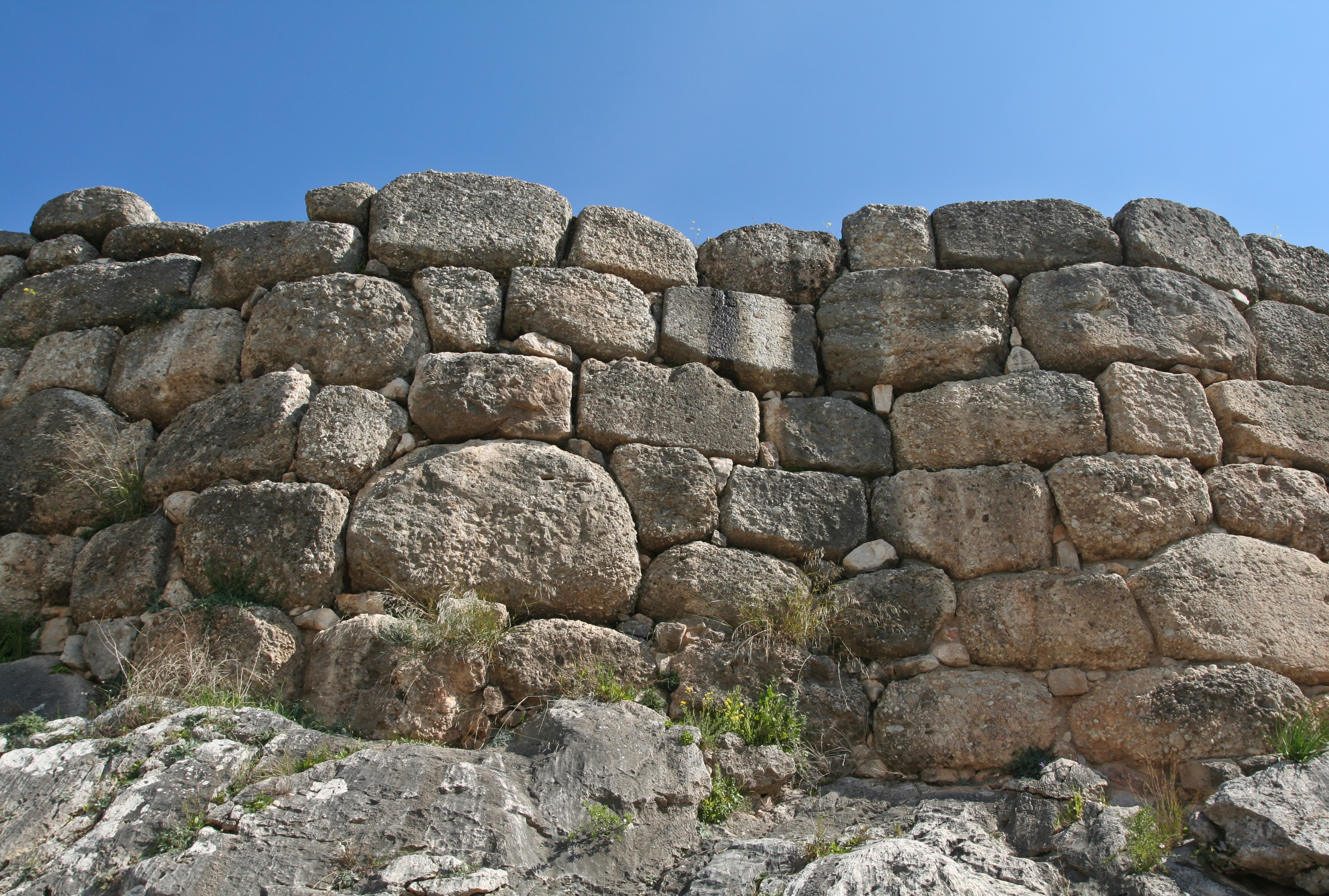A wall of gigantic rounded stones roughly shaped and placed together with a few smaller stones to fill gaps