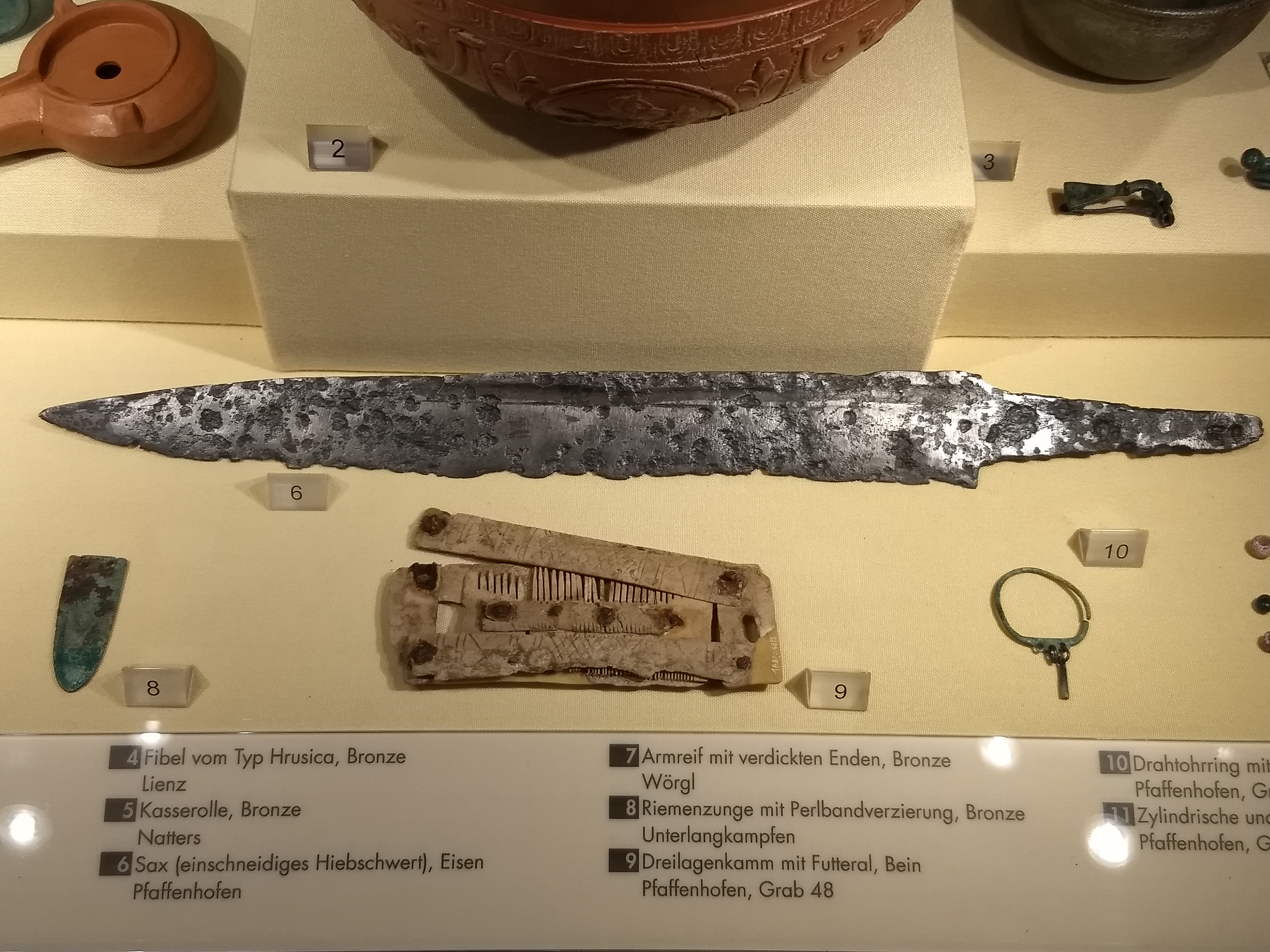A pitted sexa blade, a comb with sheaths for the teeth, a large clay pot, and some small metal dress accessories in a glass case
