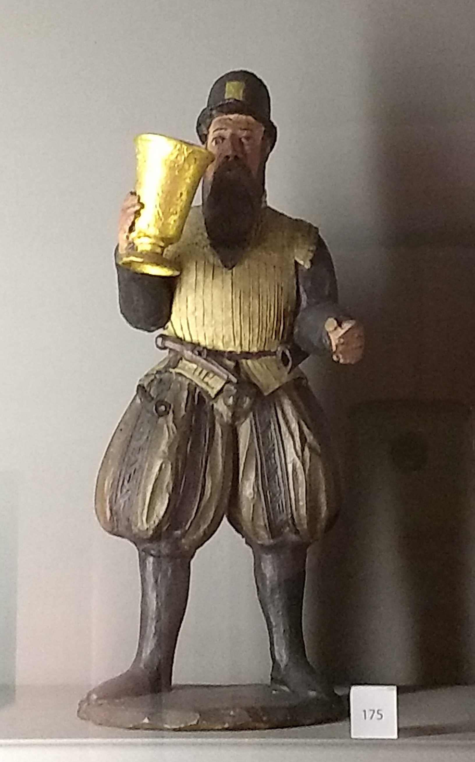 A figuring of a beareded man drinking from a large beaker. He wears boots, pluffy trunk-hose, a white leather jerkin over a doublet, and a felt hat with a brim and has a pistol and a powder horn at his belt.