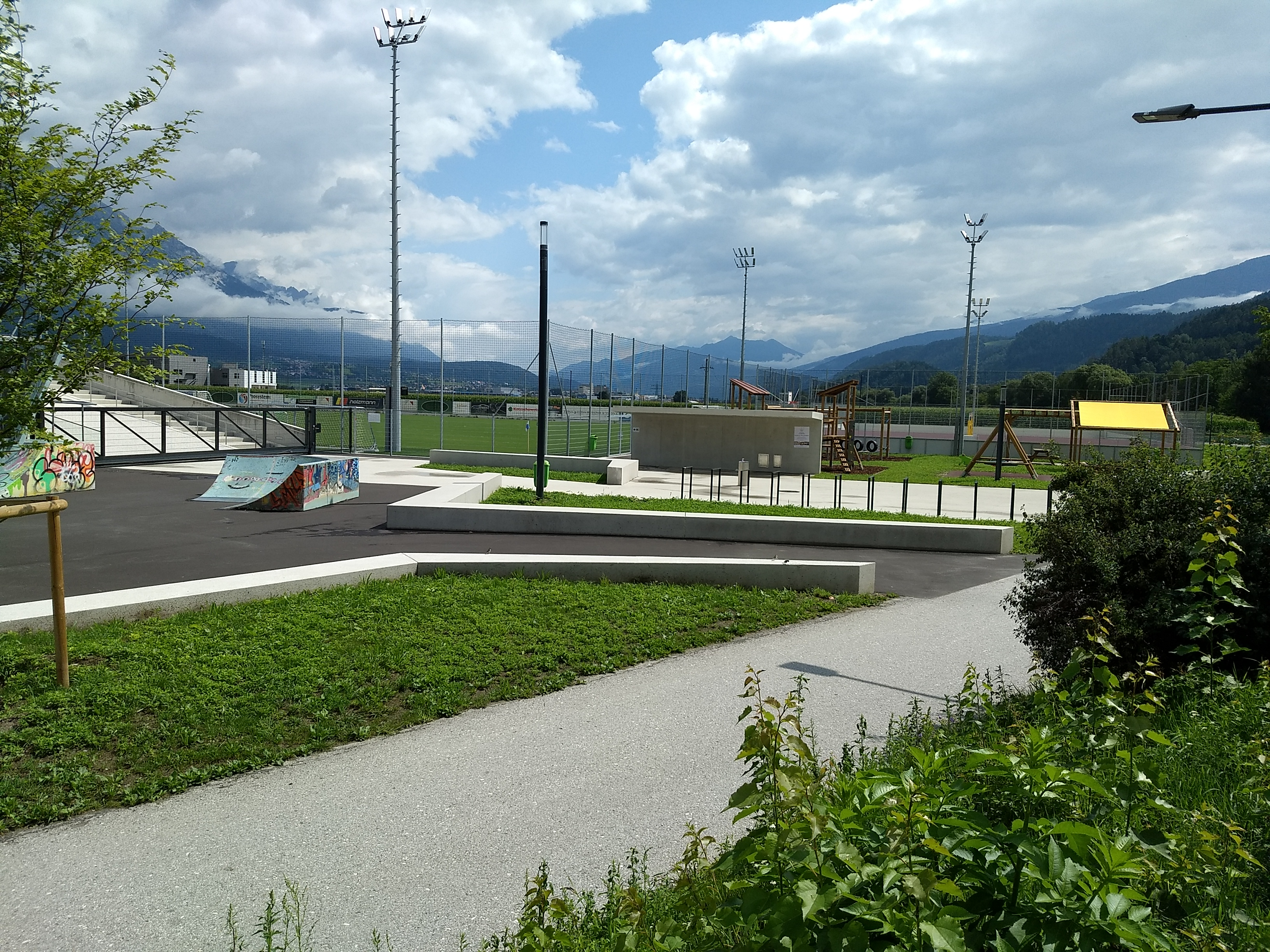 A playground with cycle trail, skateboard jumps, beach volleyball court and climbing gym.  The background is foggy mountains and a bright sky with clouds.