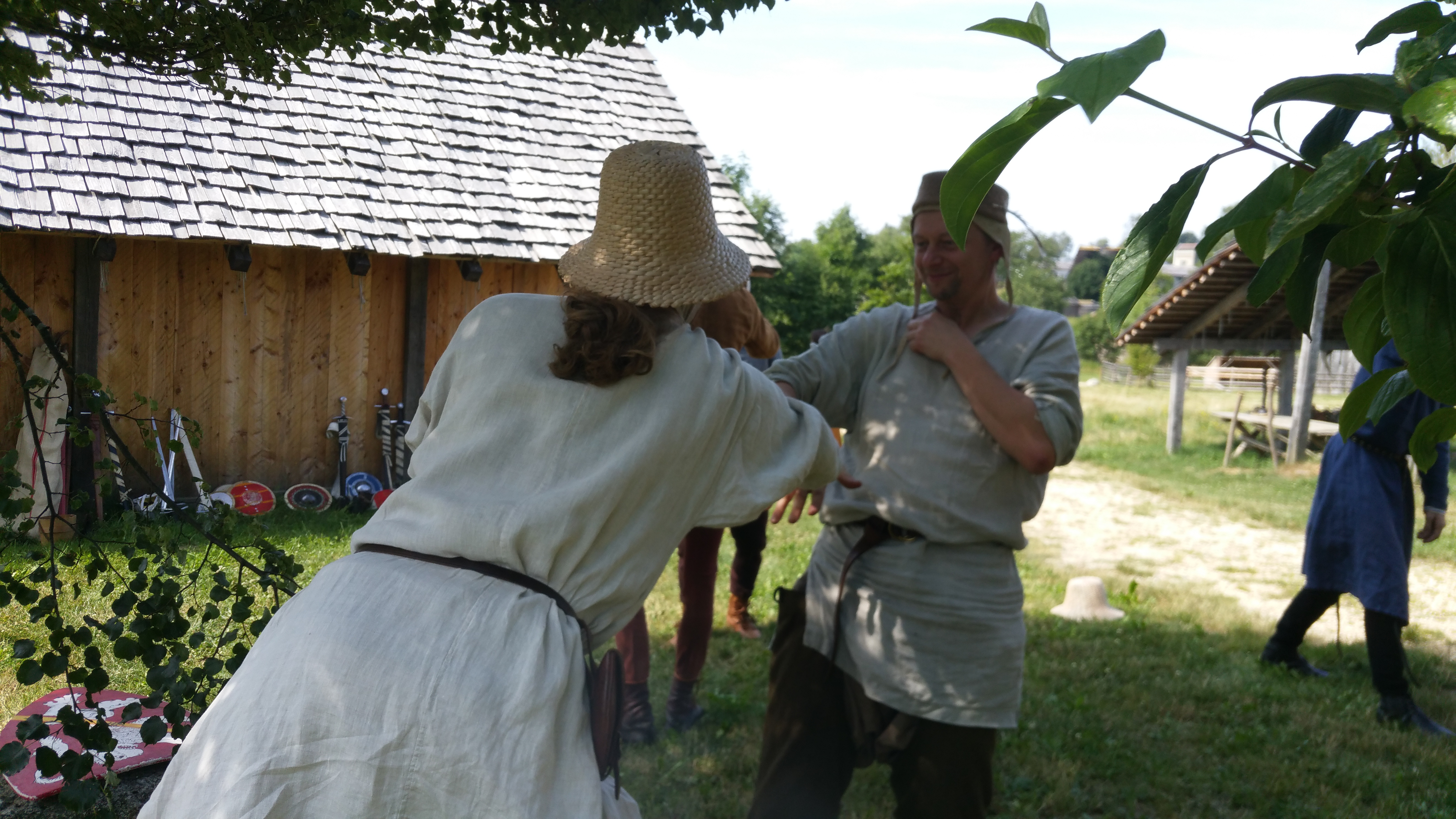 Two men in linen shirts and strraw hats playing a touch game