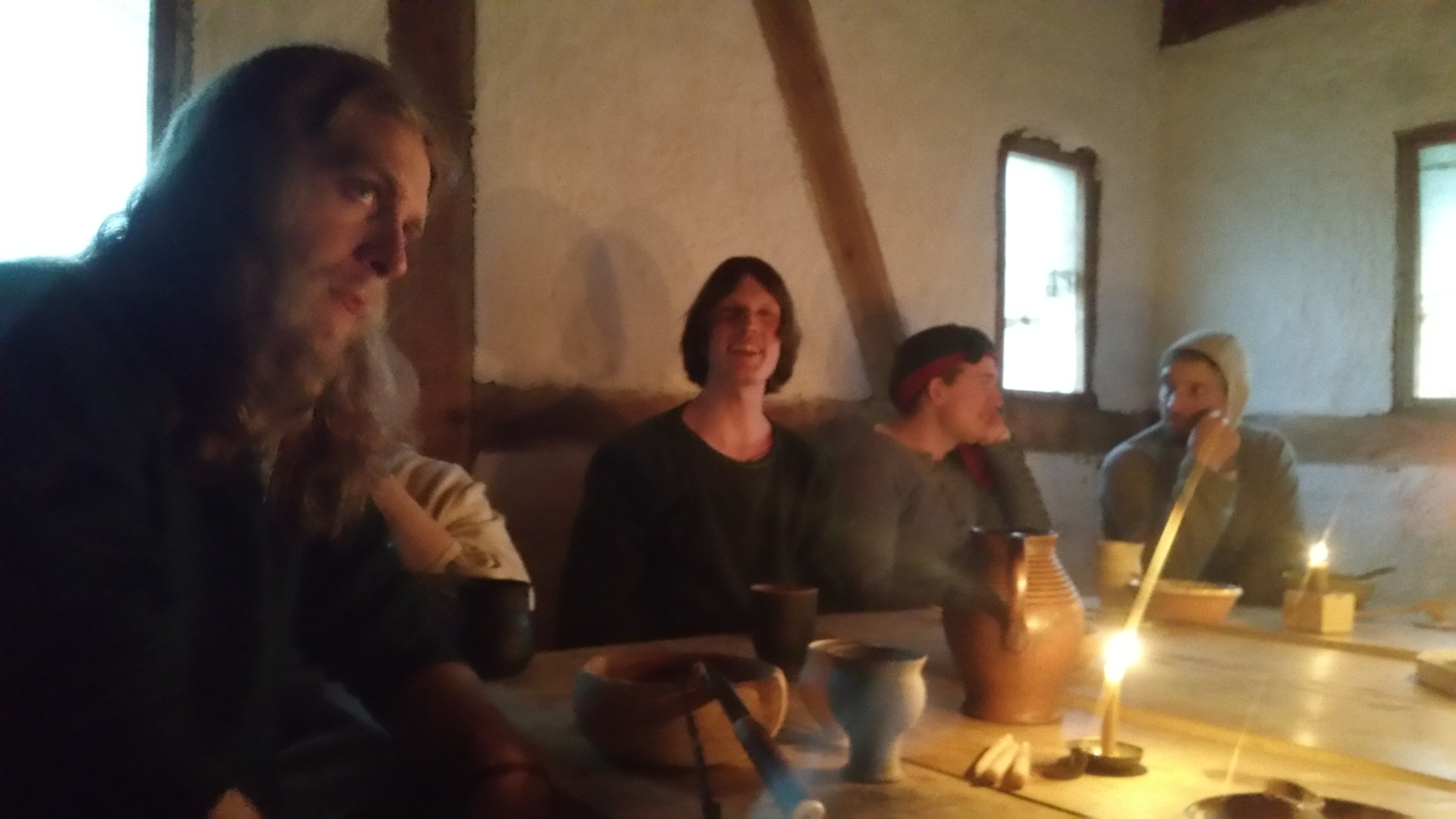 Several people sitting at a candelit table in a wattle-and-daub building