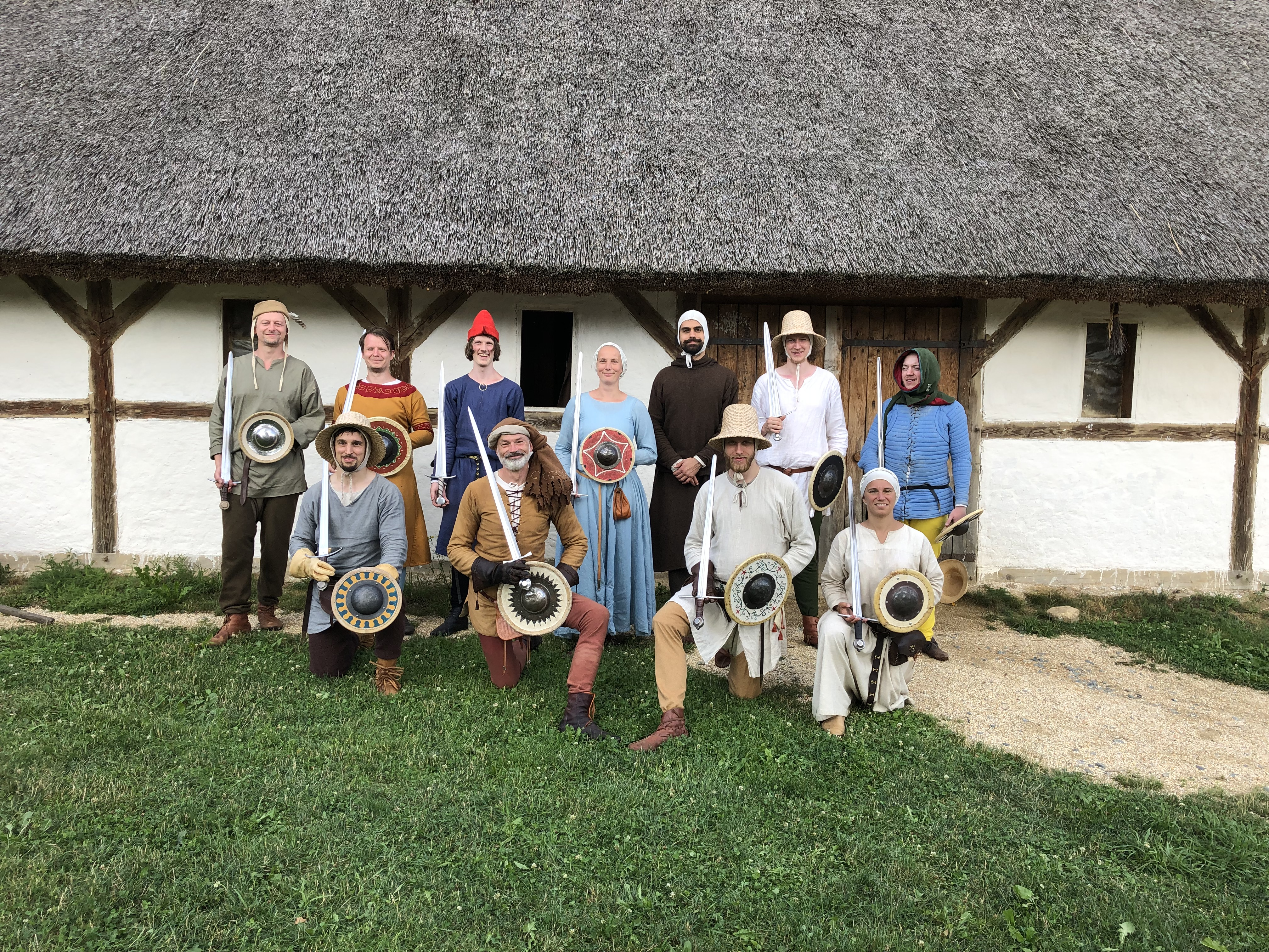 Eleven people in late medieval clothing standing in front of a wattle-and-daub building
