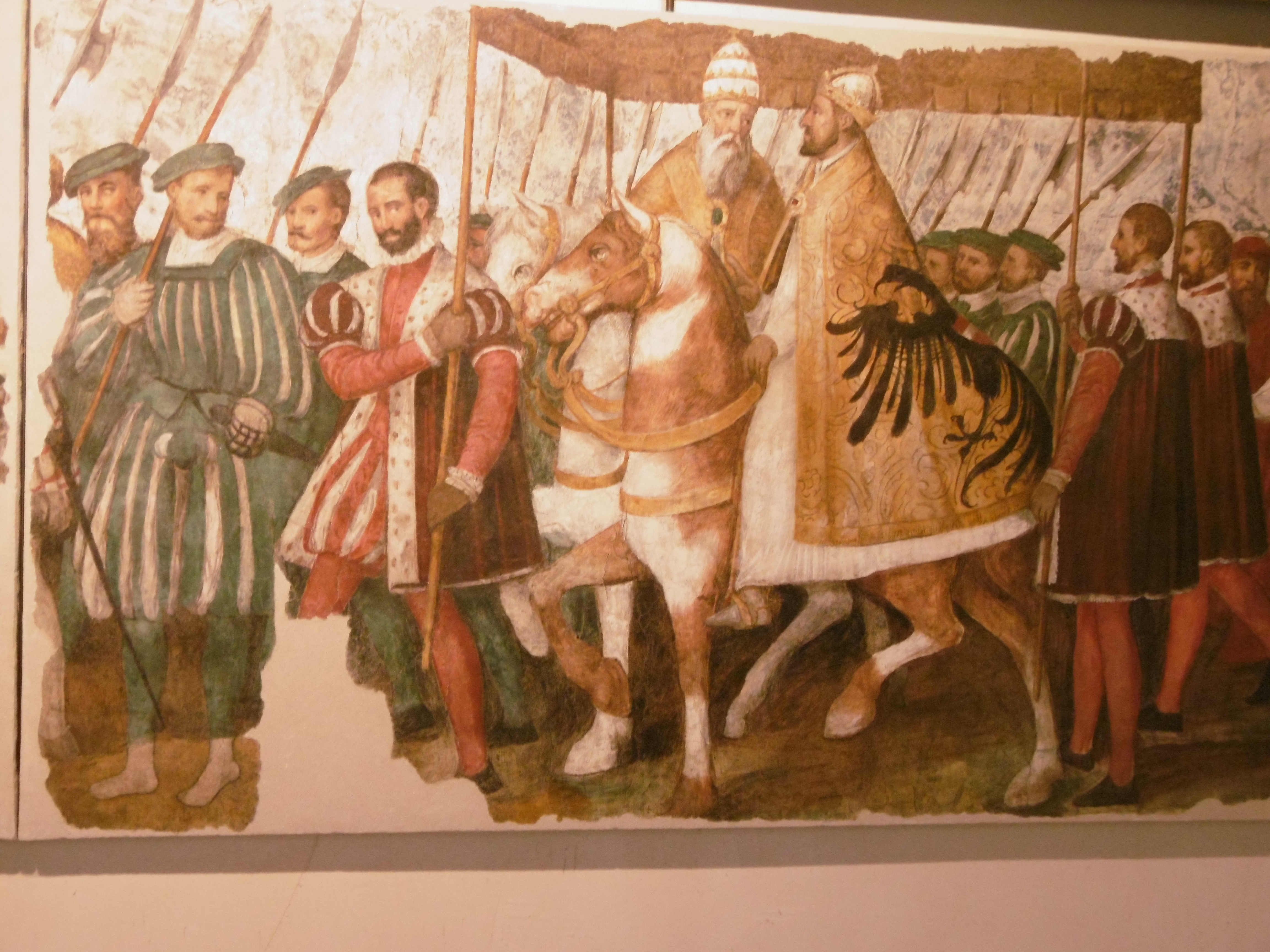 A parade of men in sixteenth-century clothing, with two horsemen in cloth-of-gold clothing under a canopy held aloft on poles