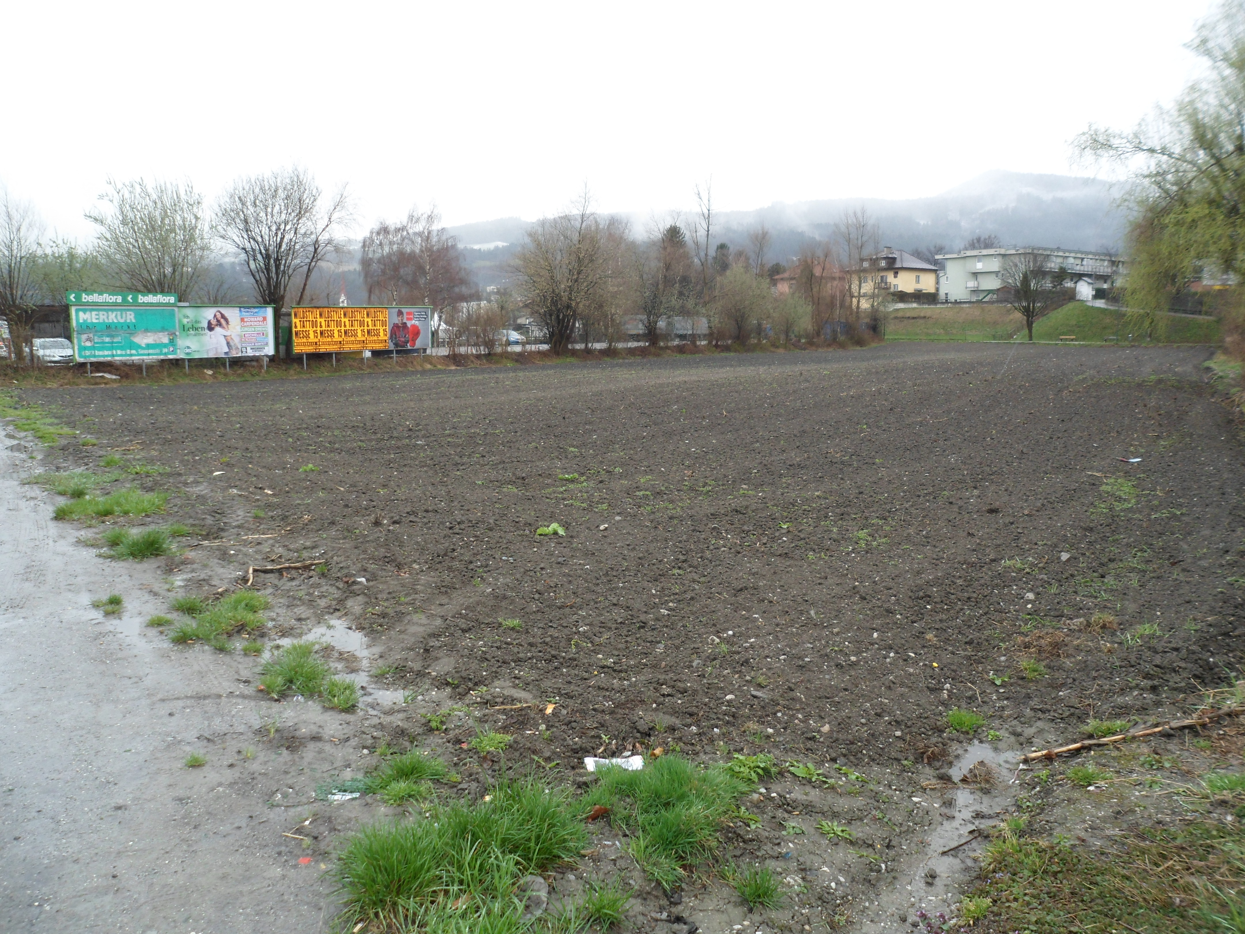 A muddy, freshly plowed field with bare trees and a fence with billboards along one side